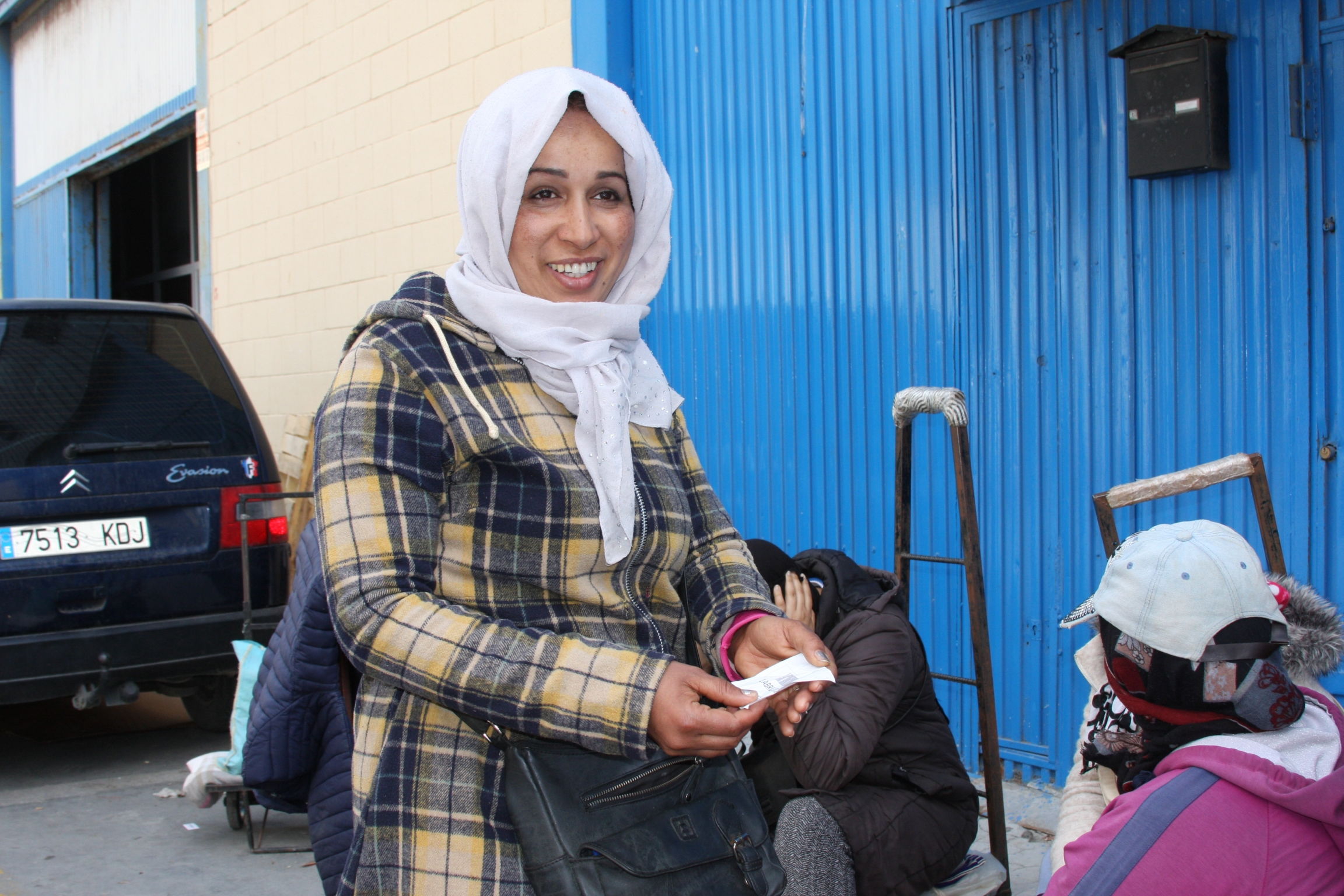 Woman in white scarf and plaid yellow jacket holds a white ticket in her hand