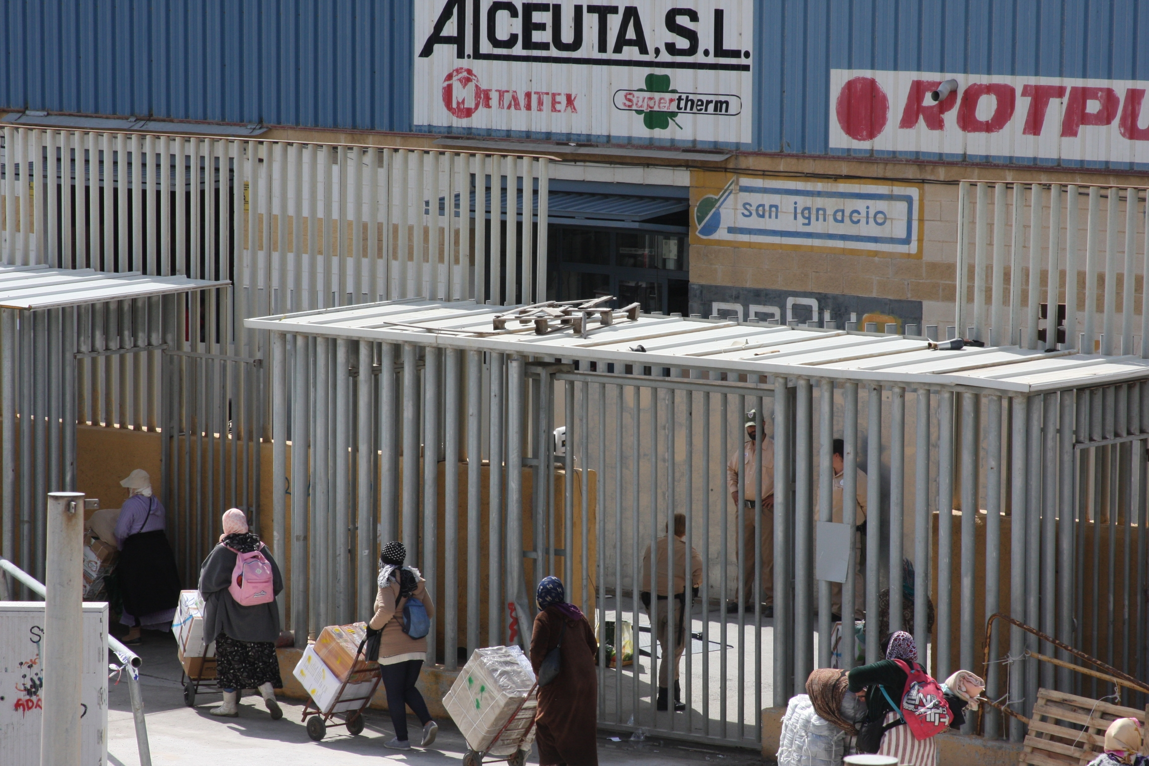 women line up to enter metal gates into spain