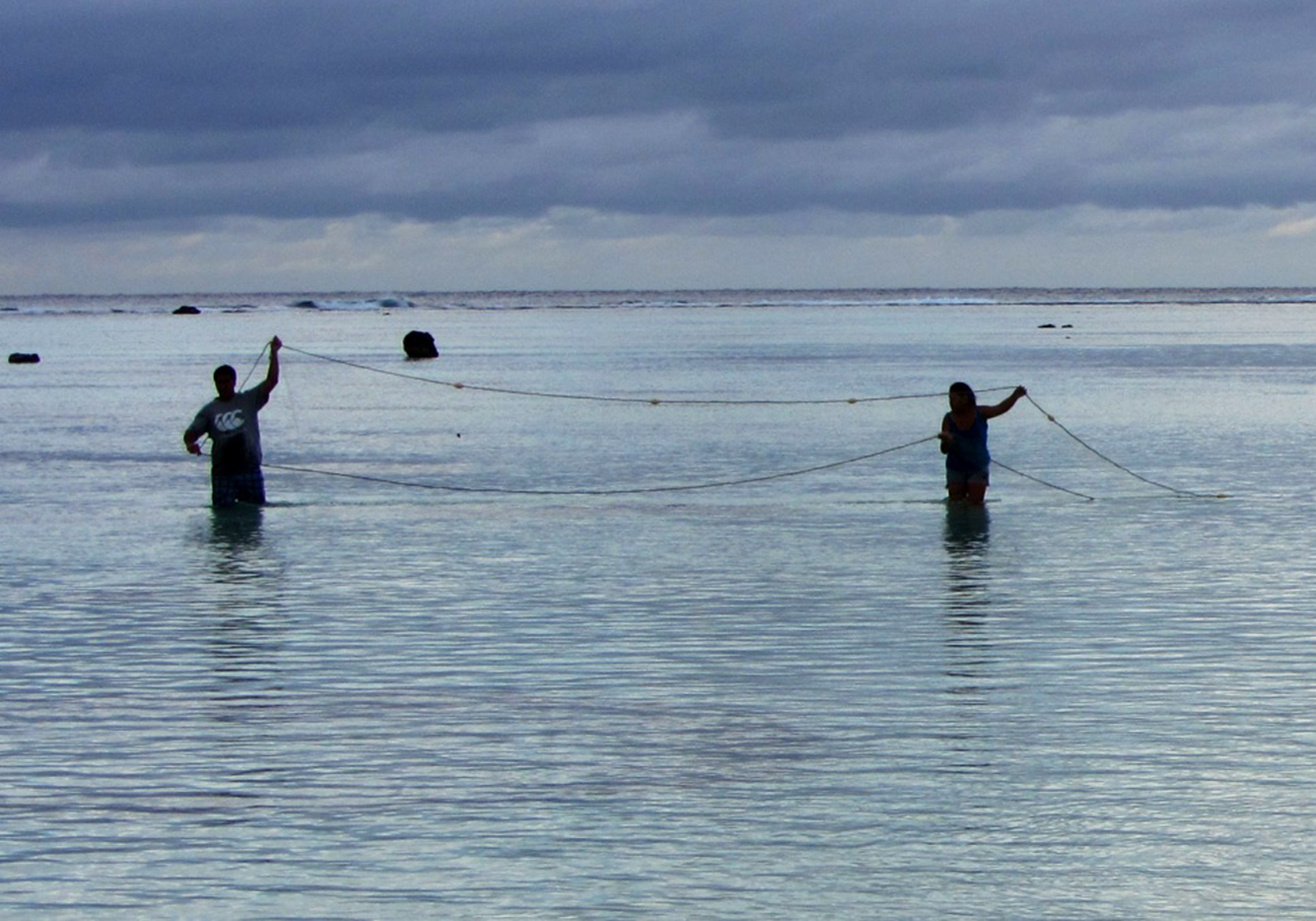 Two men in water net-fishing at dusk.