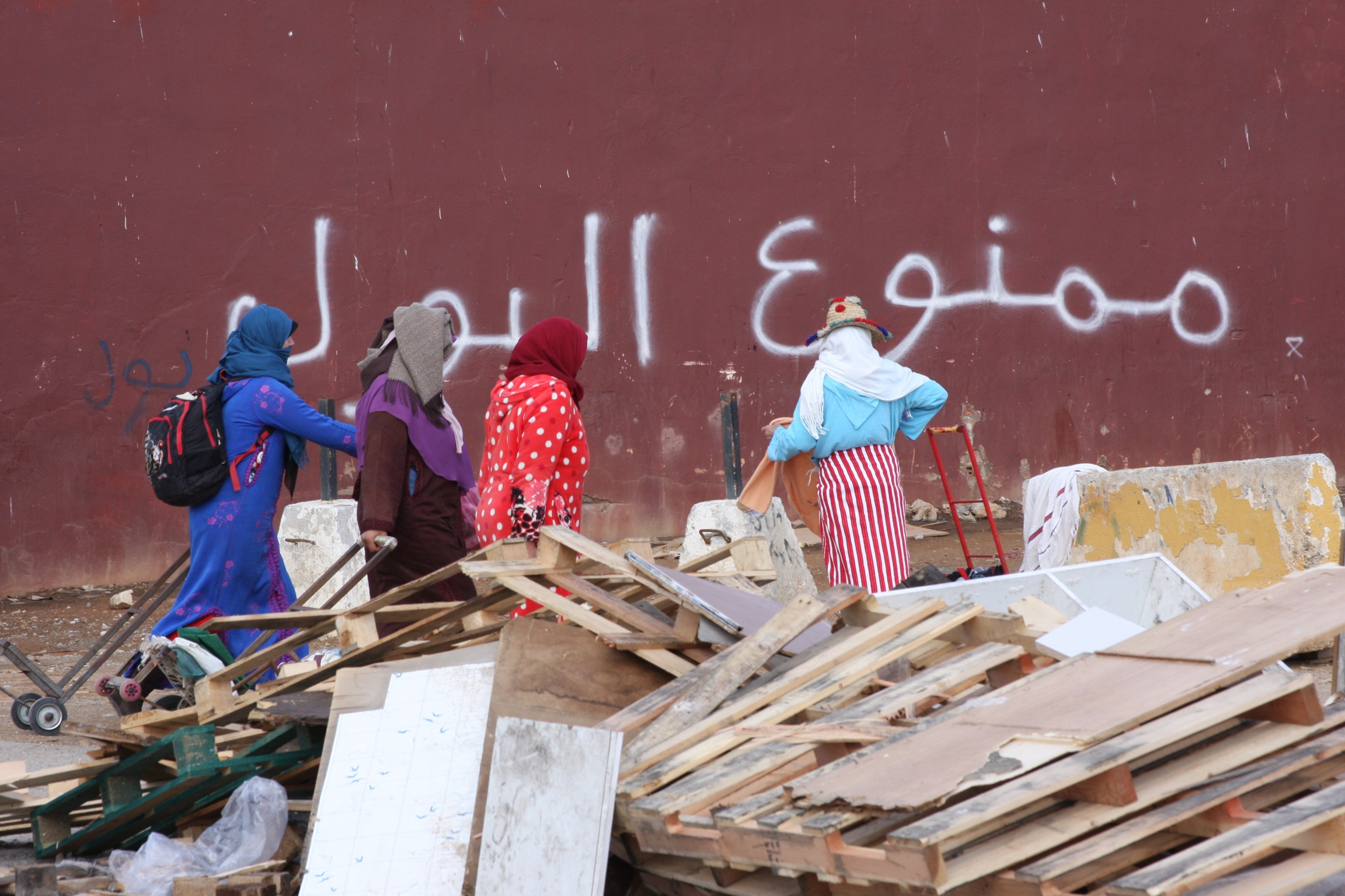 Women stand near pile of wooden debris against backdrop of red maroon wall with Arabic white letter graffitti.