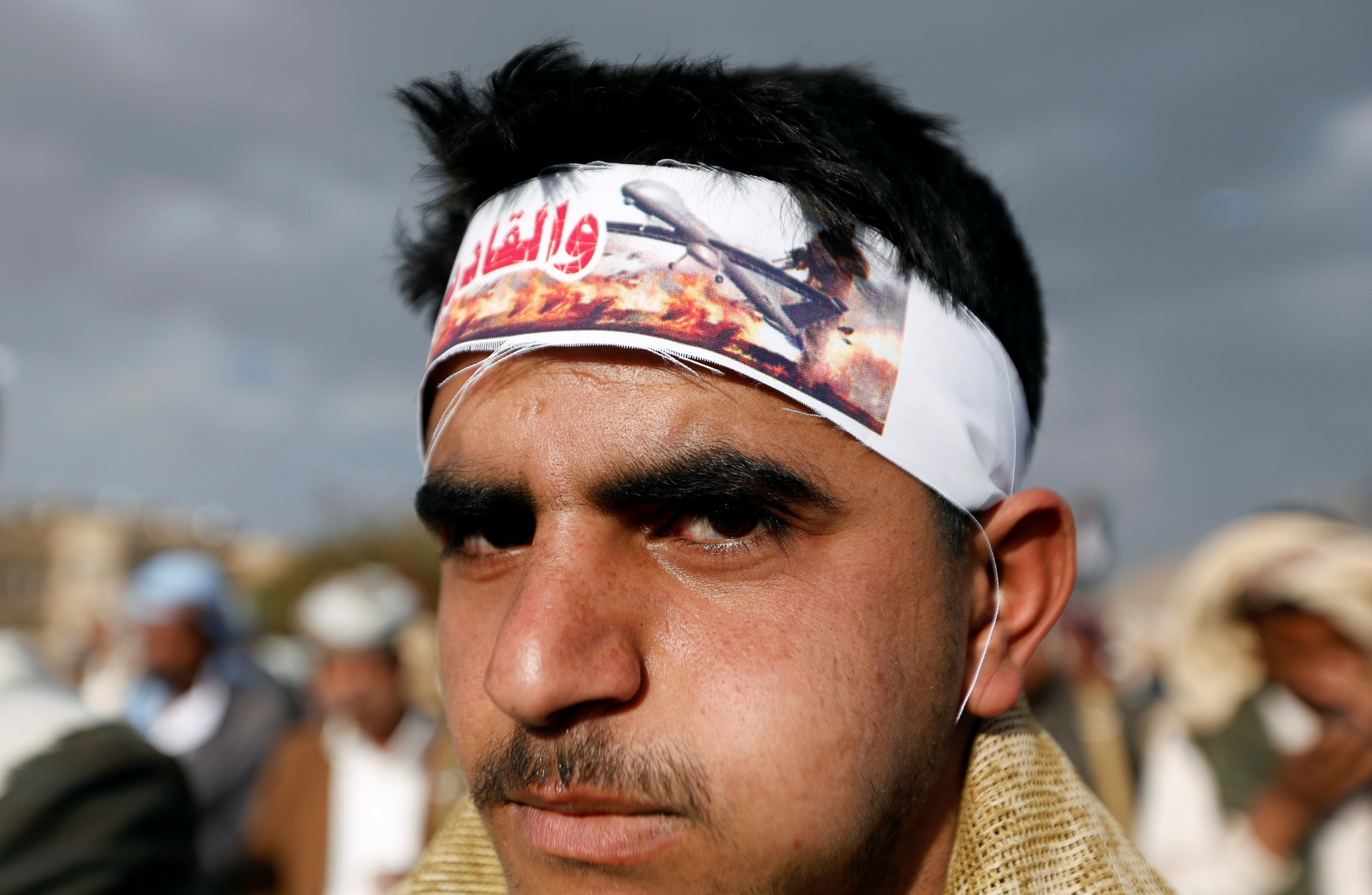 Young man wears headband showing image of drone attack