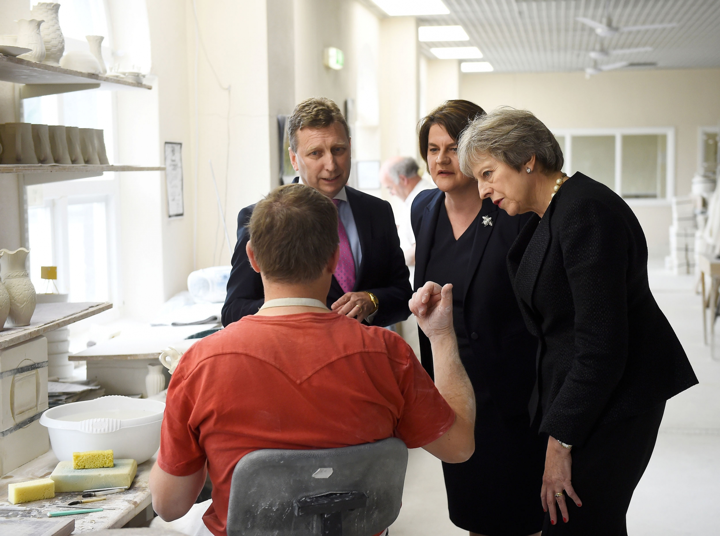 Theresa May talks to potters at a pottery gallery.