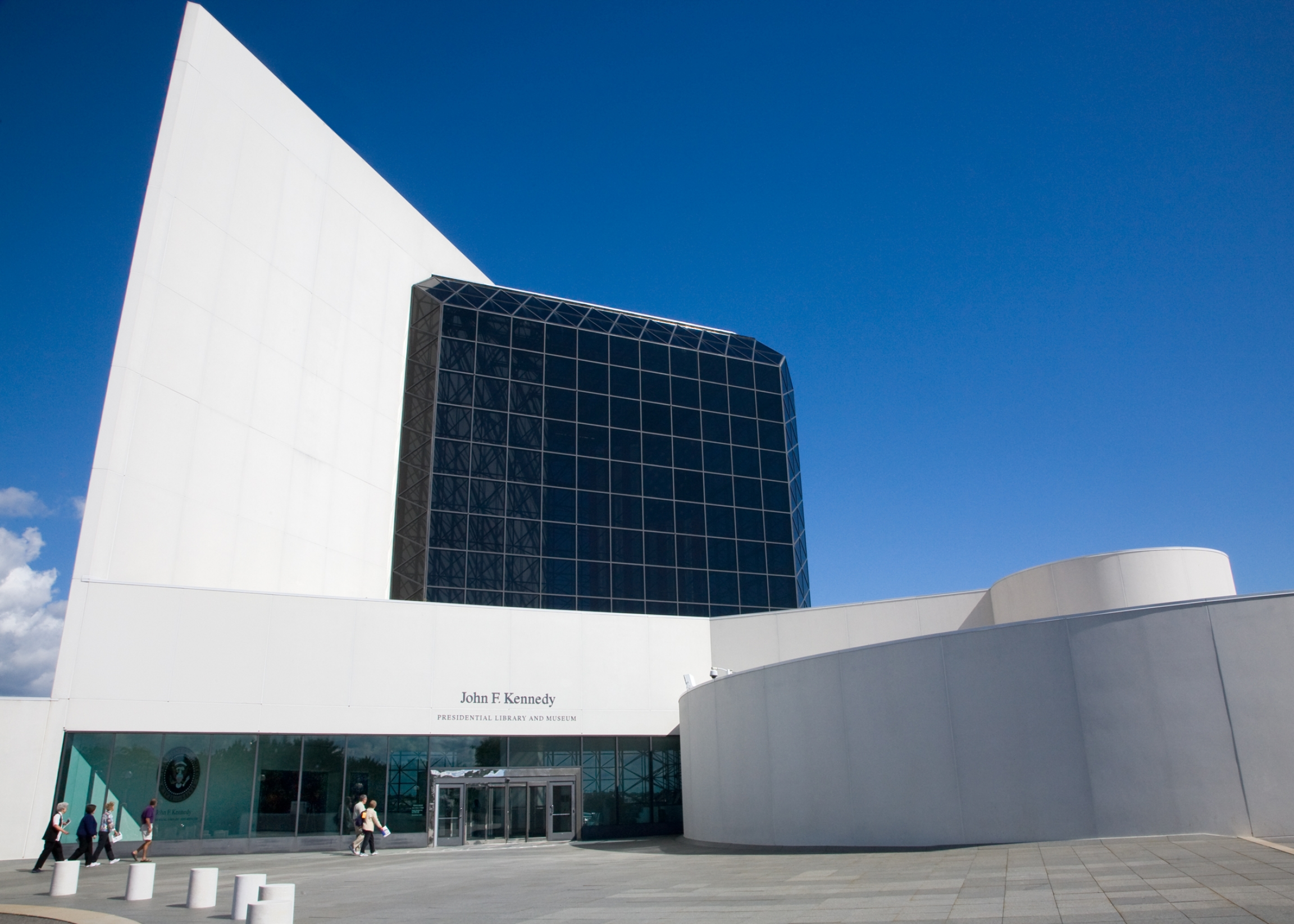 The glass and and concrete John F. Kennedy Presidential Library and Museum on a sunny day.