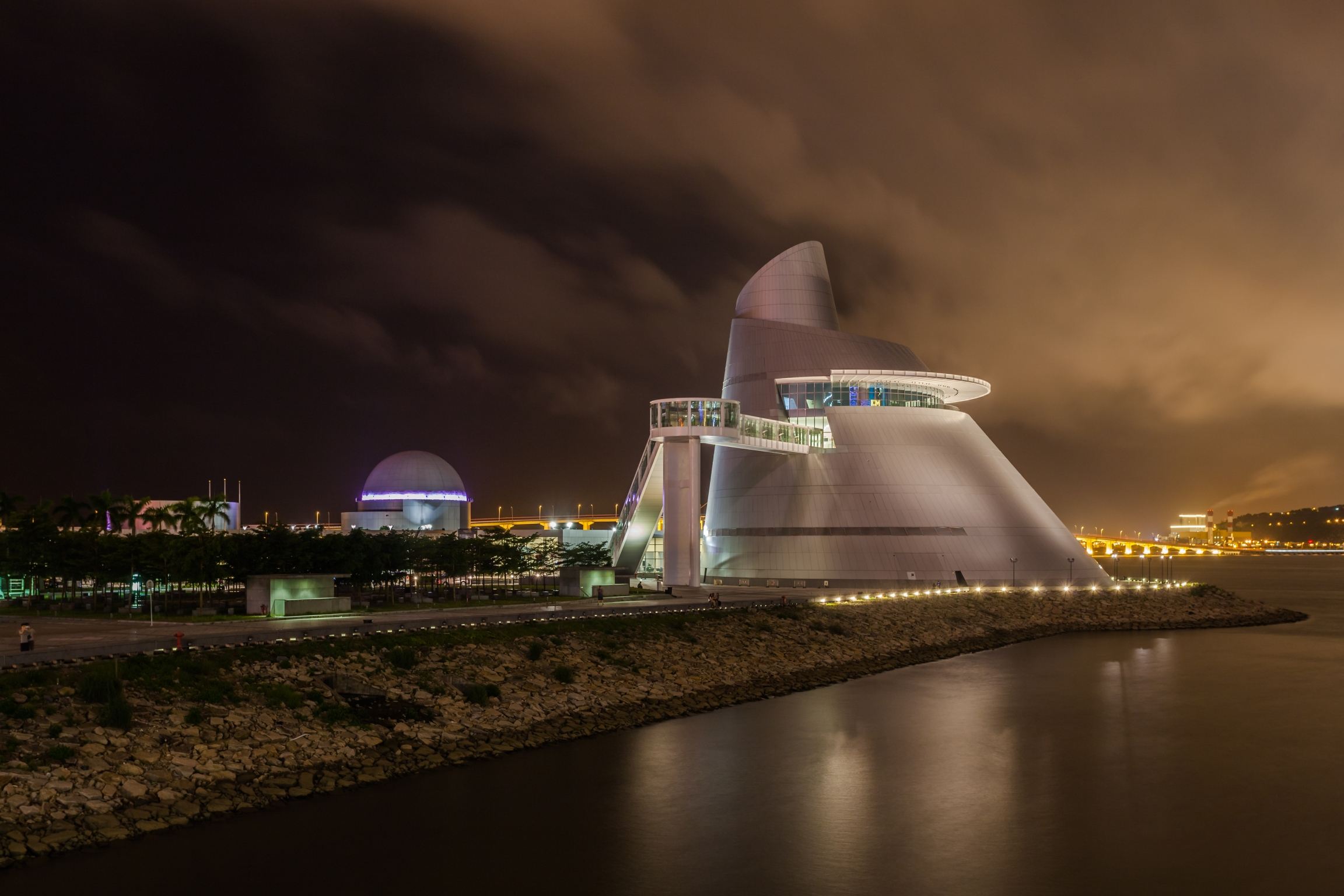 A night time view of the Macau Science Center along the water.