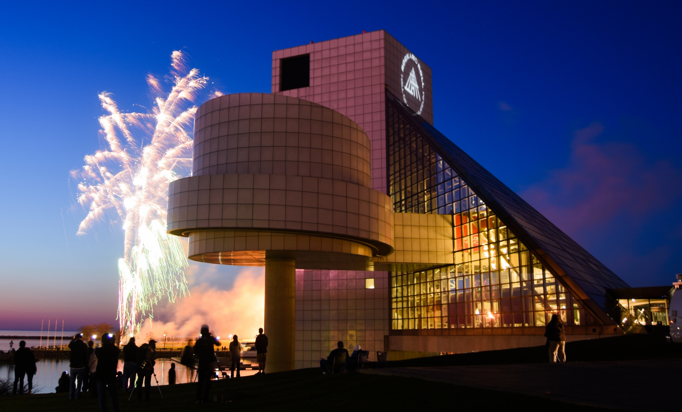 Fireworks flash next to the Rock and Roll Hall of Fame at night.