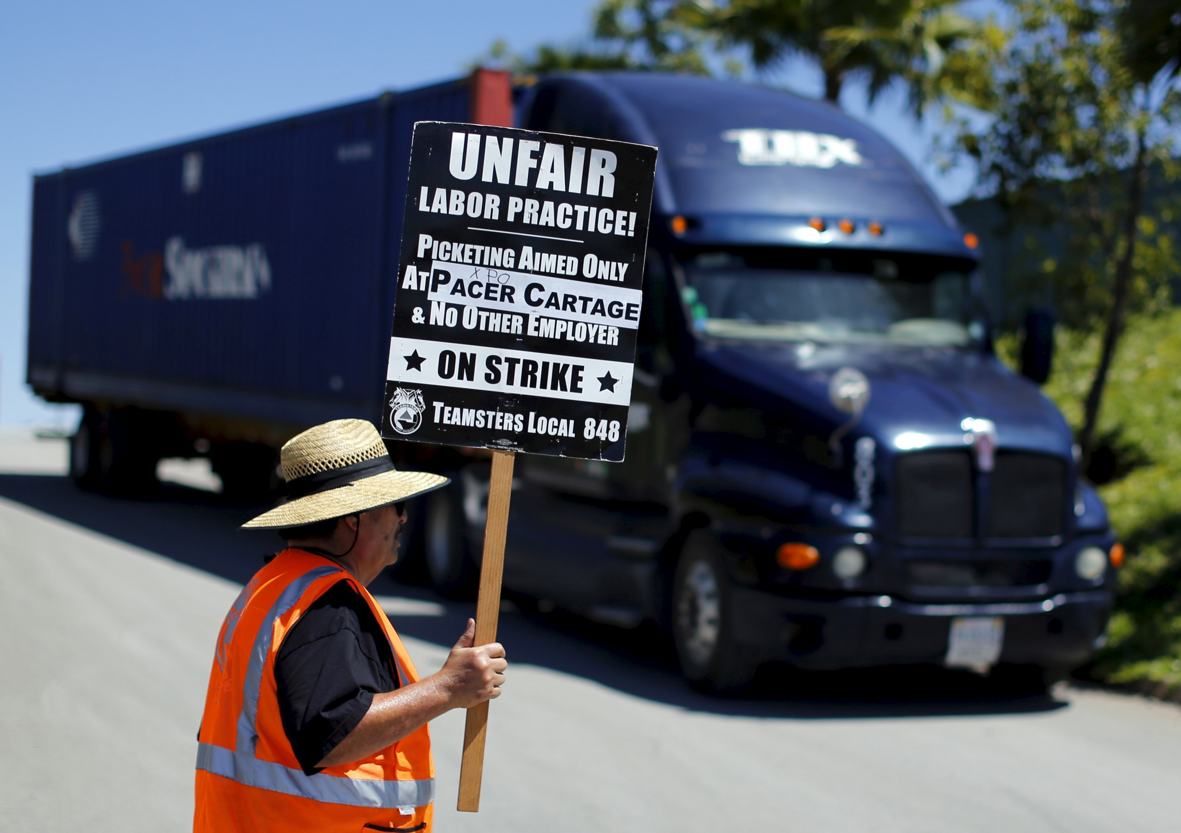 "A man next to a truck stands in an orange vest with a sign that says ""unfair labor practice."""