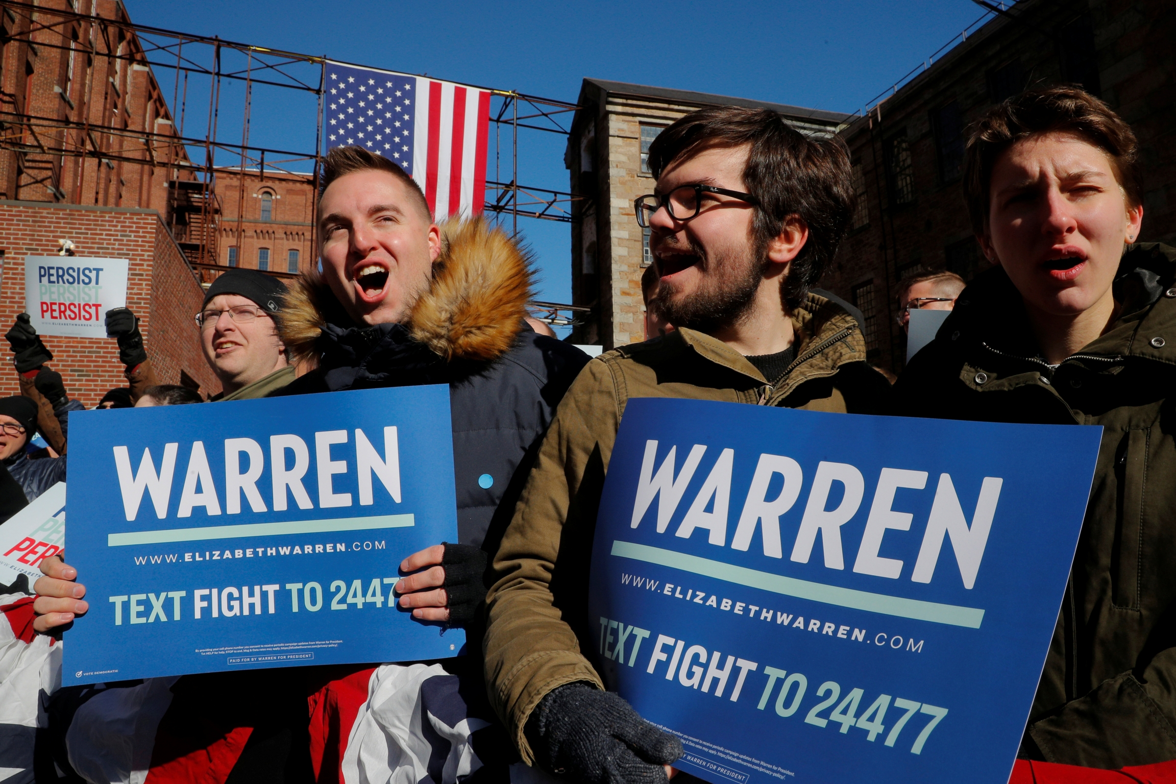 Young men hold campaign signs for Elizabeth Warren.