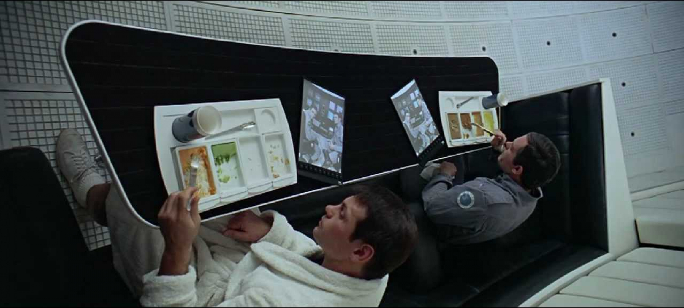 """Dr. Francis Poole and Commander David Bowman watch a news segment about their mission on iPad-like screens in Stanley Kubrick's """"2001: A Space Odyssey."""""""