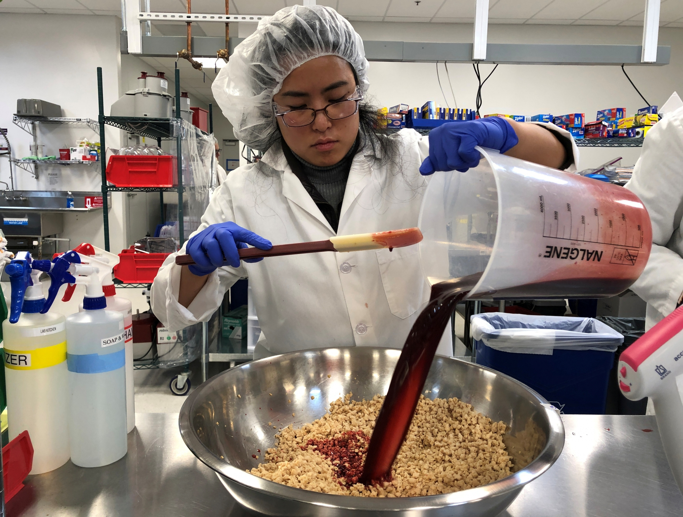 Impossible Foods research technician Alexia Yue pours a heme solution, the key ingredient, into a plant-based mixture for burgers at the company's facility in Redwood City, California.March 26, 2019.