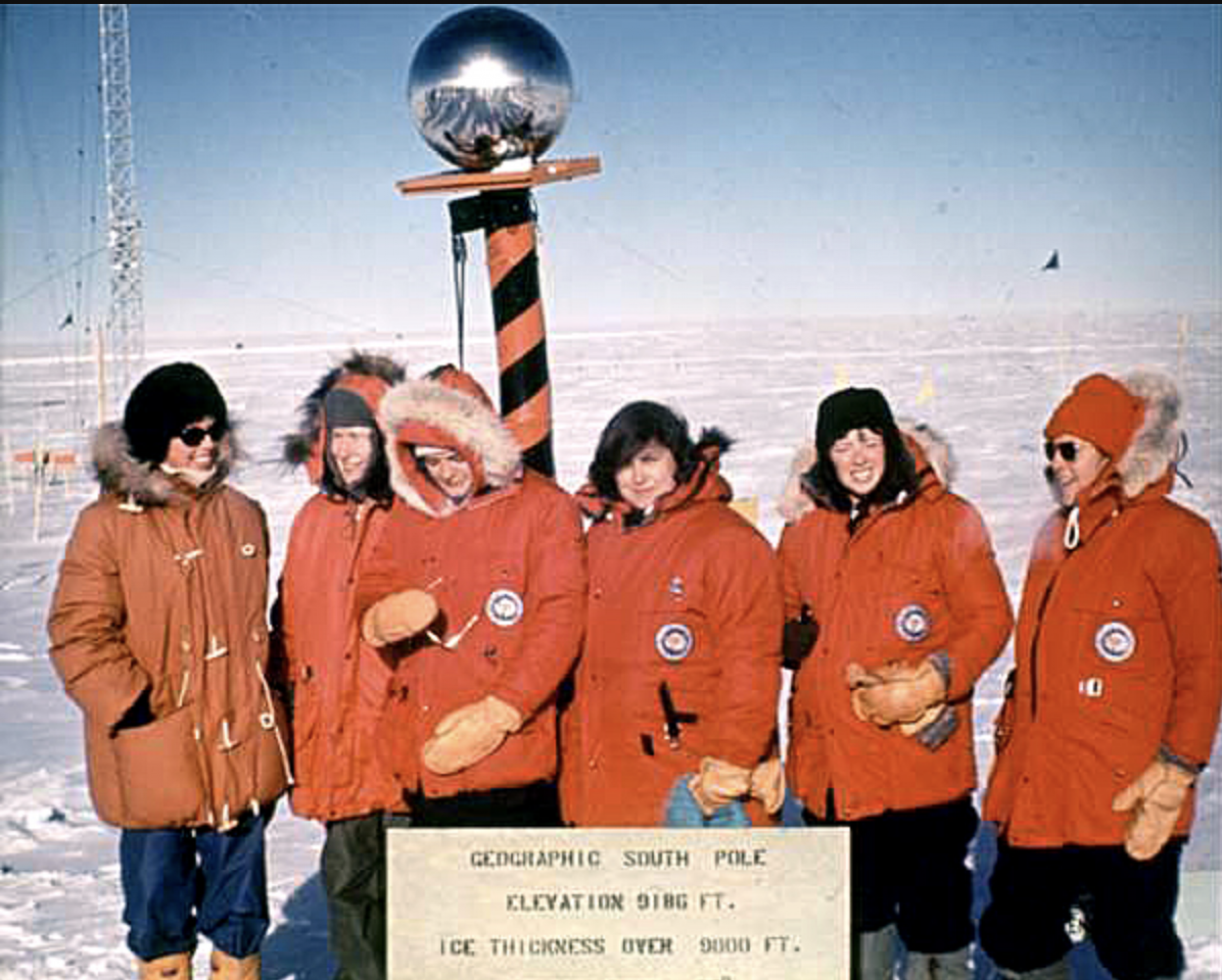 Five women with red parkas pose for a photo at the South Pole.