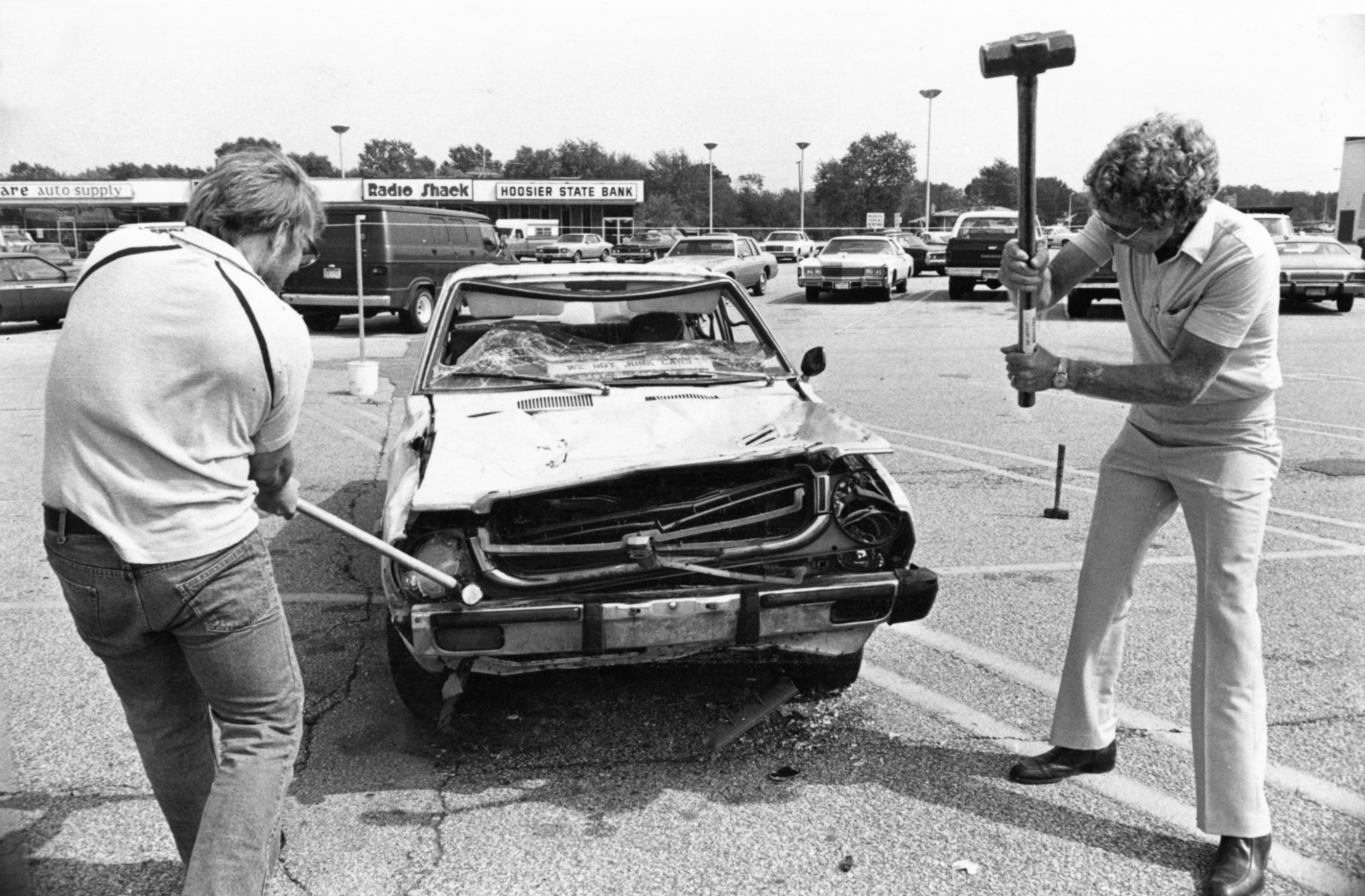 Auto worker Jim Coleman (left) and businessman Charlie Cobb (right) swing sledgehammers in Indiana at a Japanese-made car for $1 a shot. The money went to help the families of laid-off workers, Friday, Sept. 10, 1982.