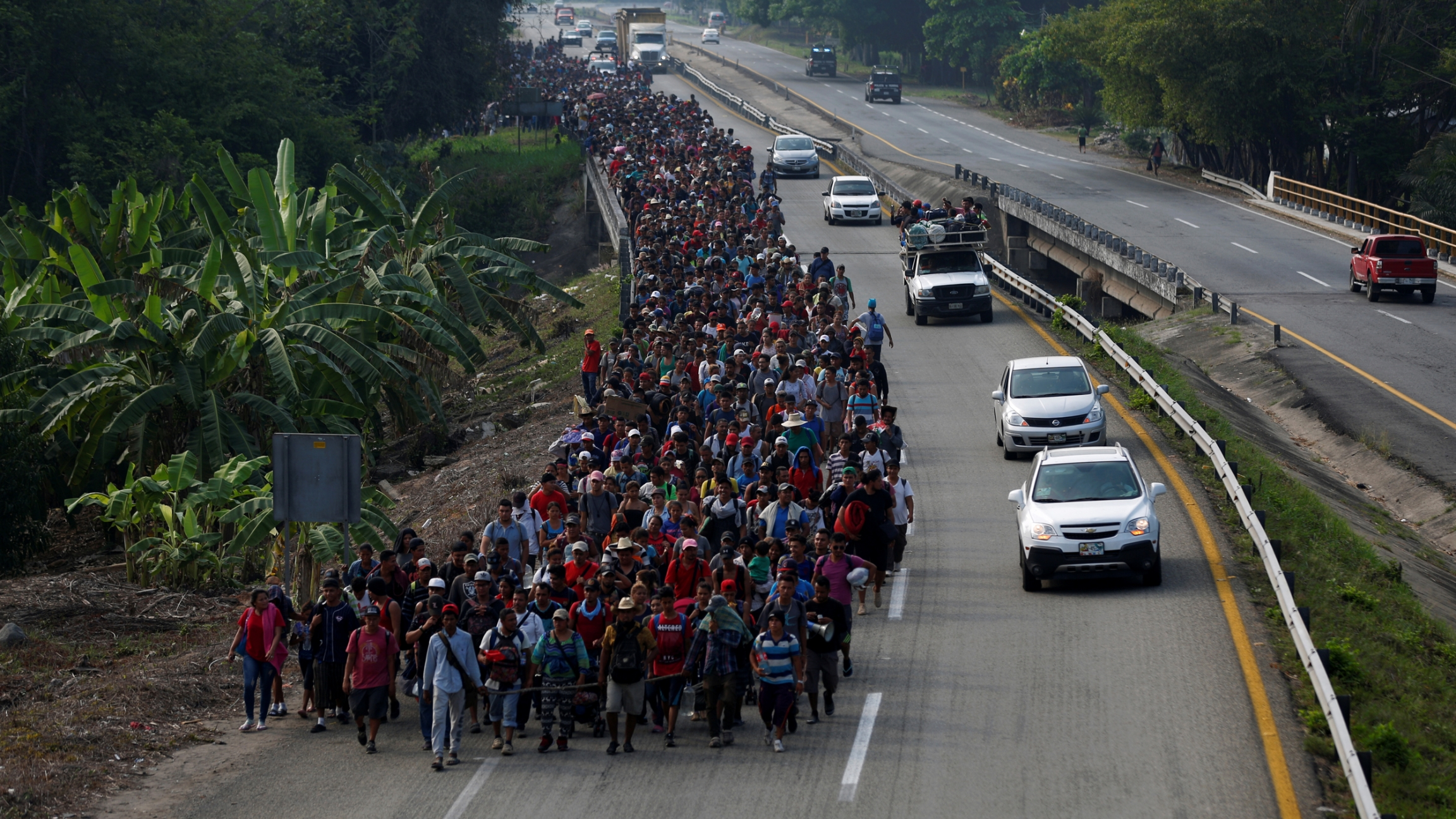 A long line of people, hundreds and hundreds, walk in one lane of a highway in a large mass.