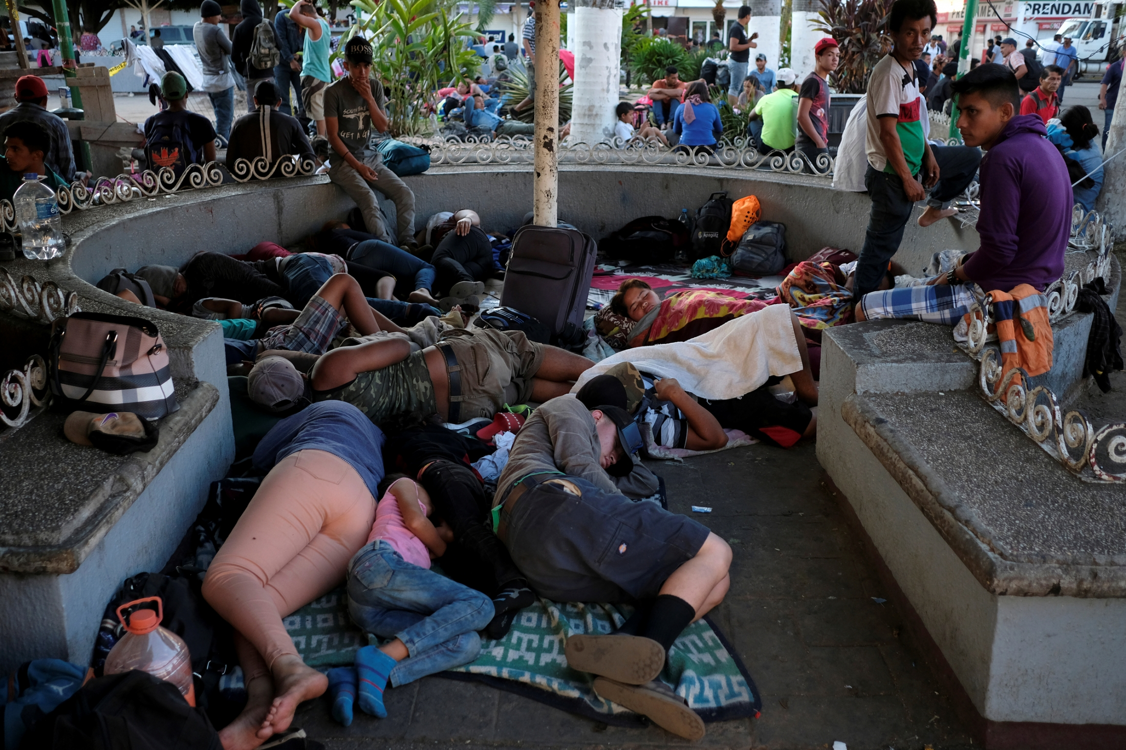 A group of people sleep in a concrete structure in a public park
