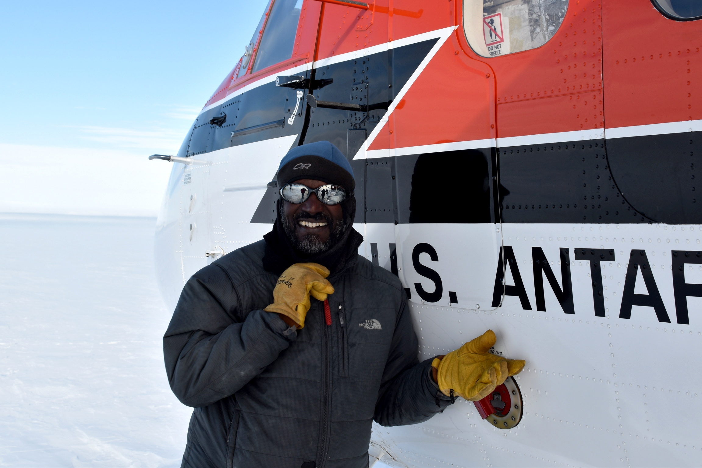 A man smiles in a posed photo in front of a Twin Otter airplane.