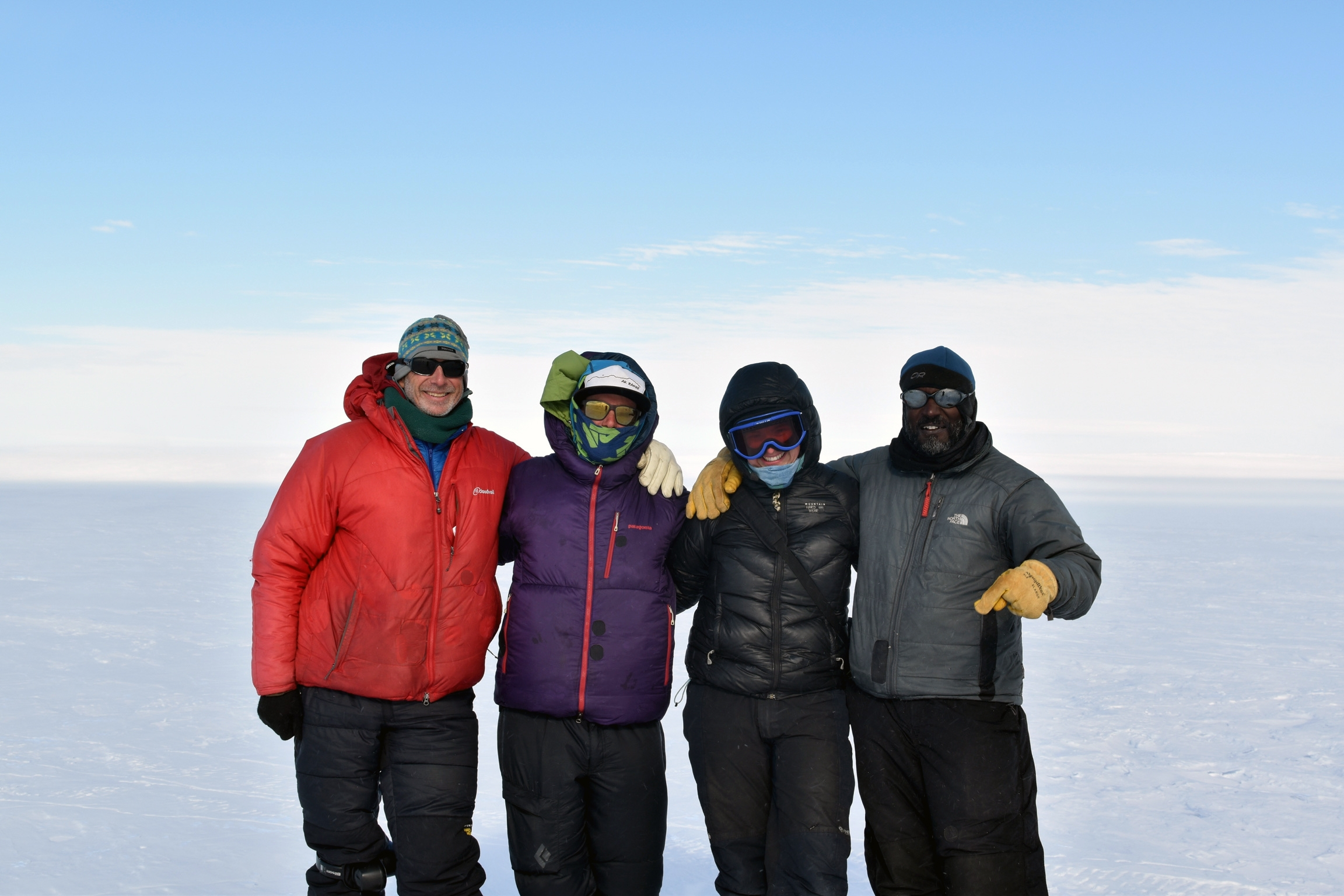 A group of four people pose in cold weather gear. Behind them is a white, icy horizon.