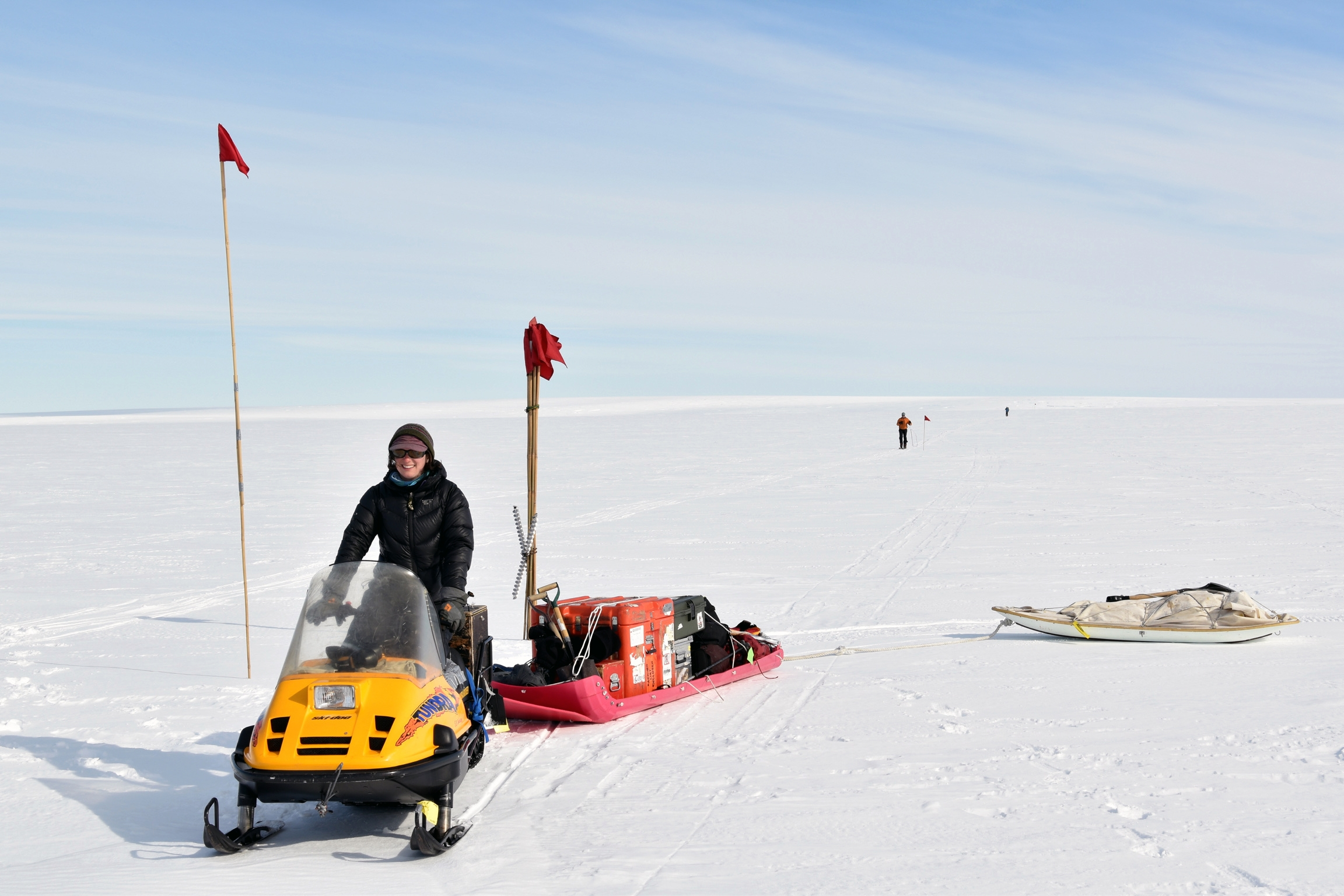 A woman steers a snowmobile towing equipment across the icy landscape.