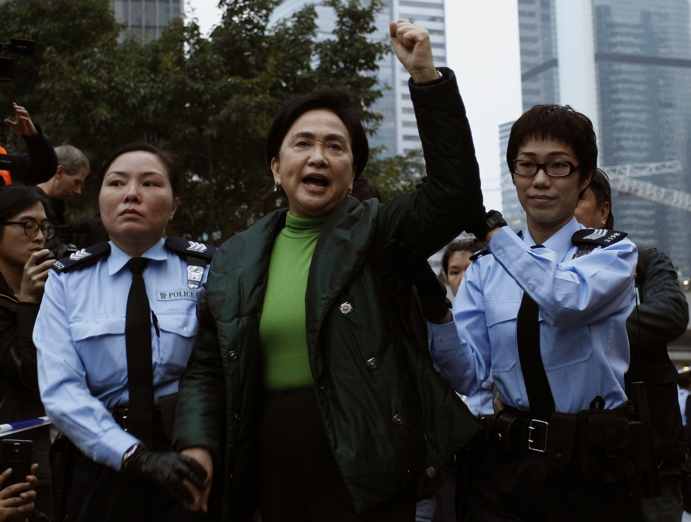Emily Lau chants slogans as she is taken away by the police outside the government headquarters in Hong Kong December 11, 2014.