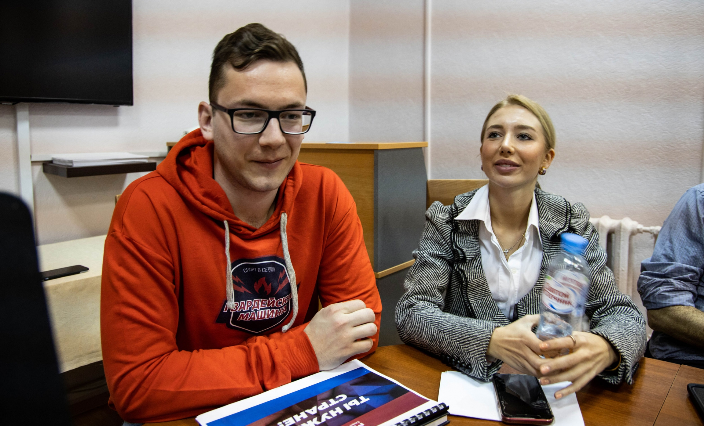 Two young people sit at a table. One young man is wearing an orange hoodie with Russian words on it.