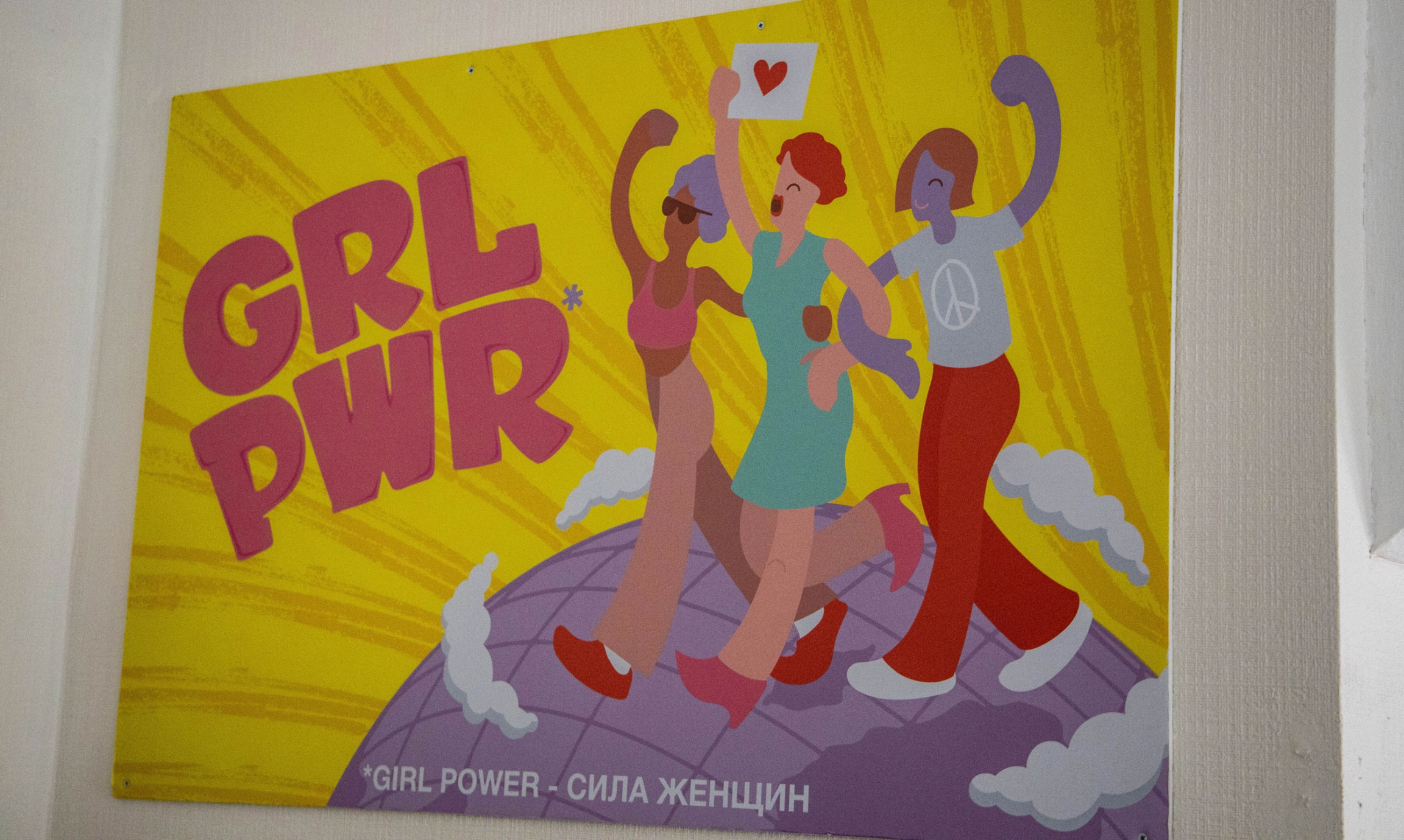 An illustrated poster shows three women linked arm in arm walking on a globe and it says GRL PWR.