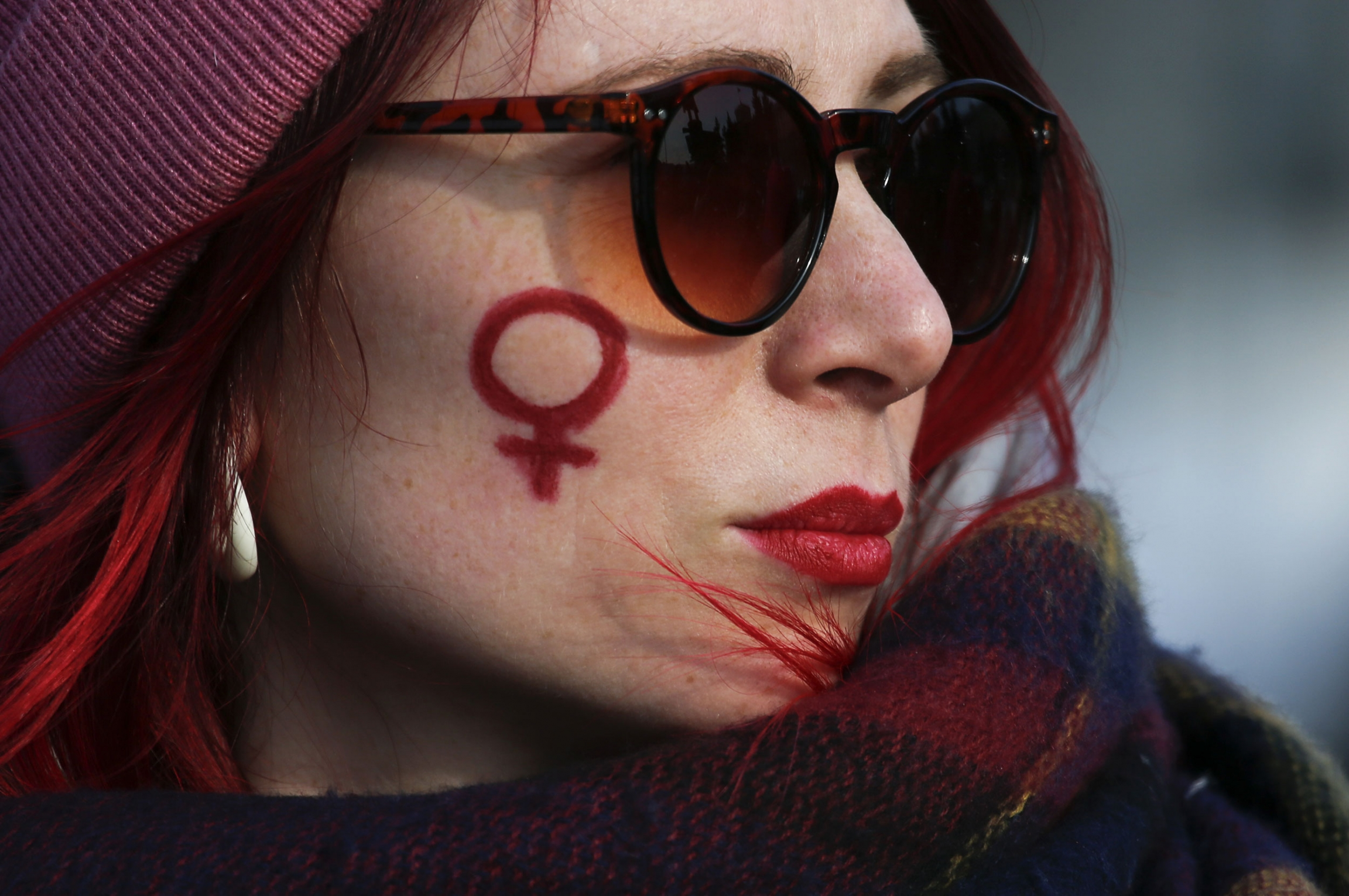 A woman has drawn the symbol for women on her cheek