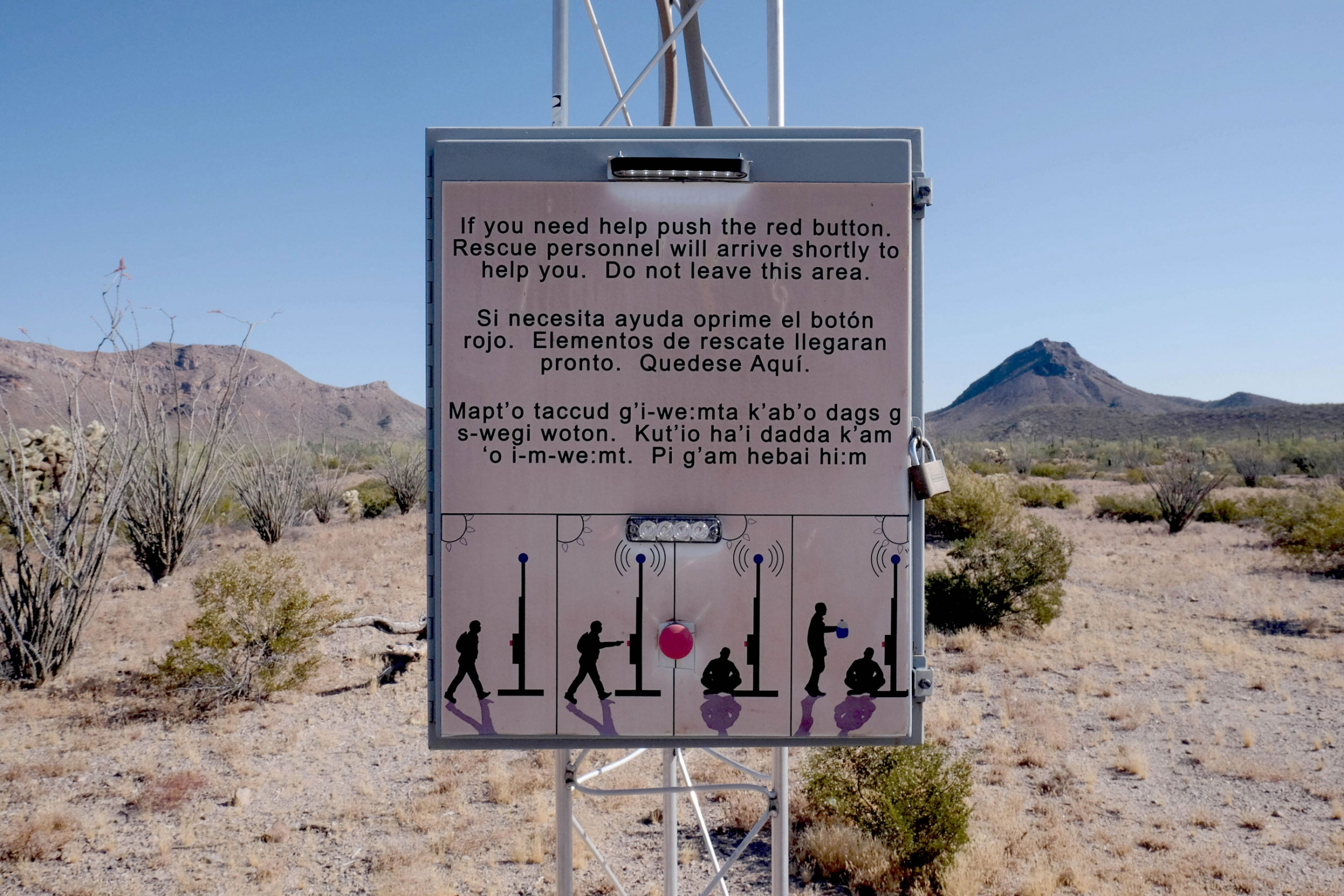 "A sign in the desert reads, ""If you need help push the red button. Rescue personnel will arrive shortly to help you. Do not leave this area."""