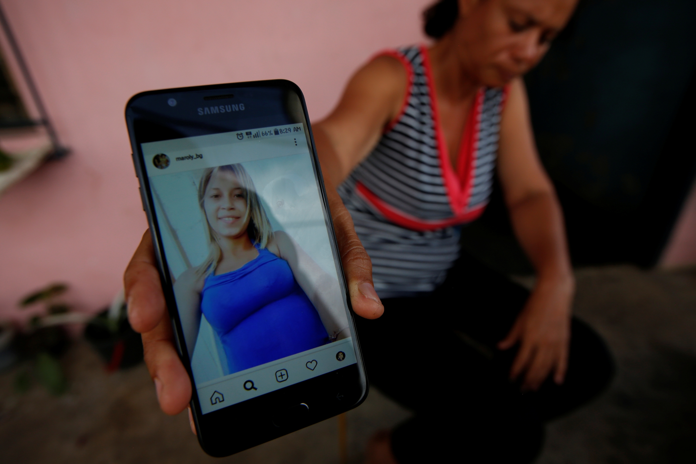 a mother shows a picture of her missing daughter