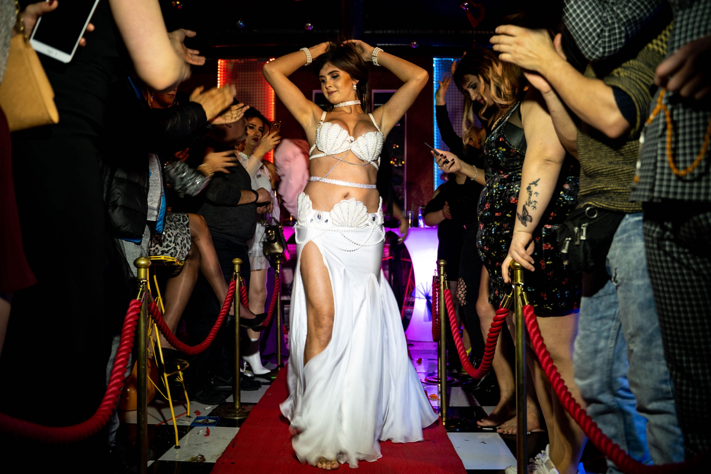 A transgender woman in shown wearing a white dress and baring her midriff.