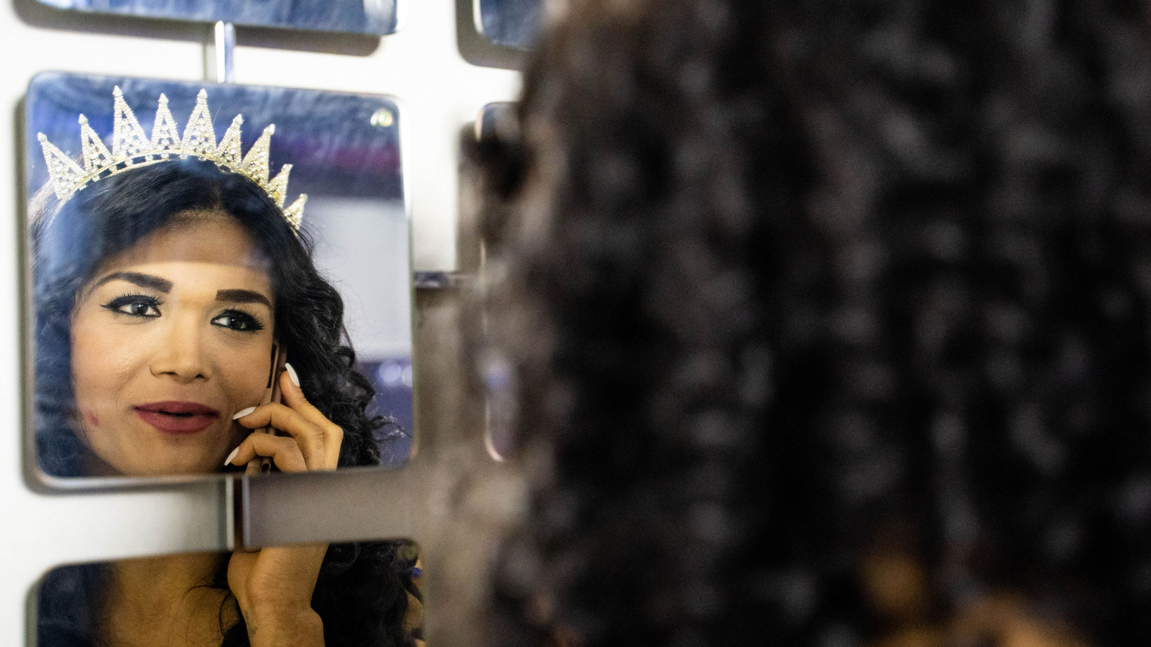 A transgender woman is shown in the reflection of a mirror holding a phone to her hear and wearing a crown.