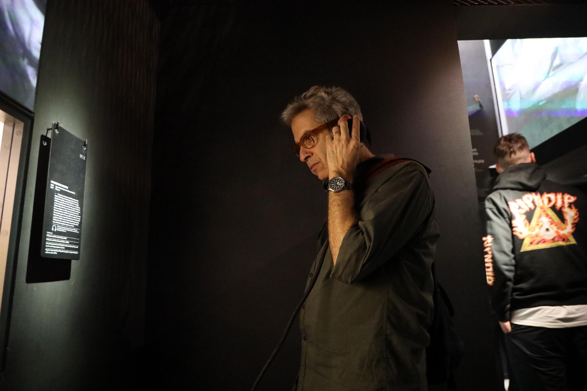 A man stands in a dark museum