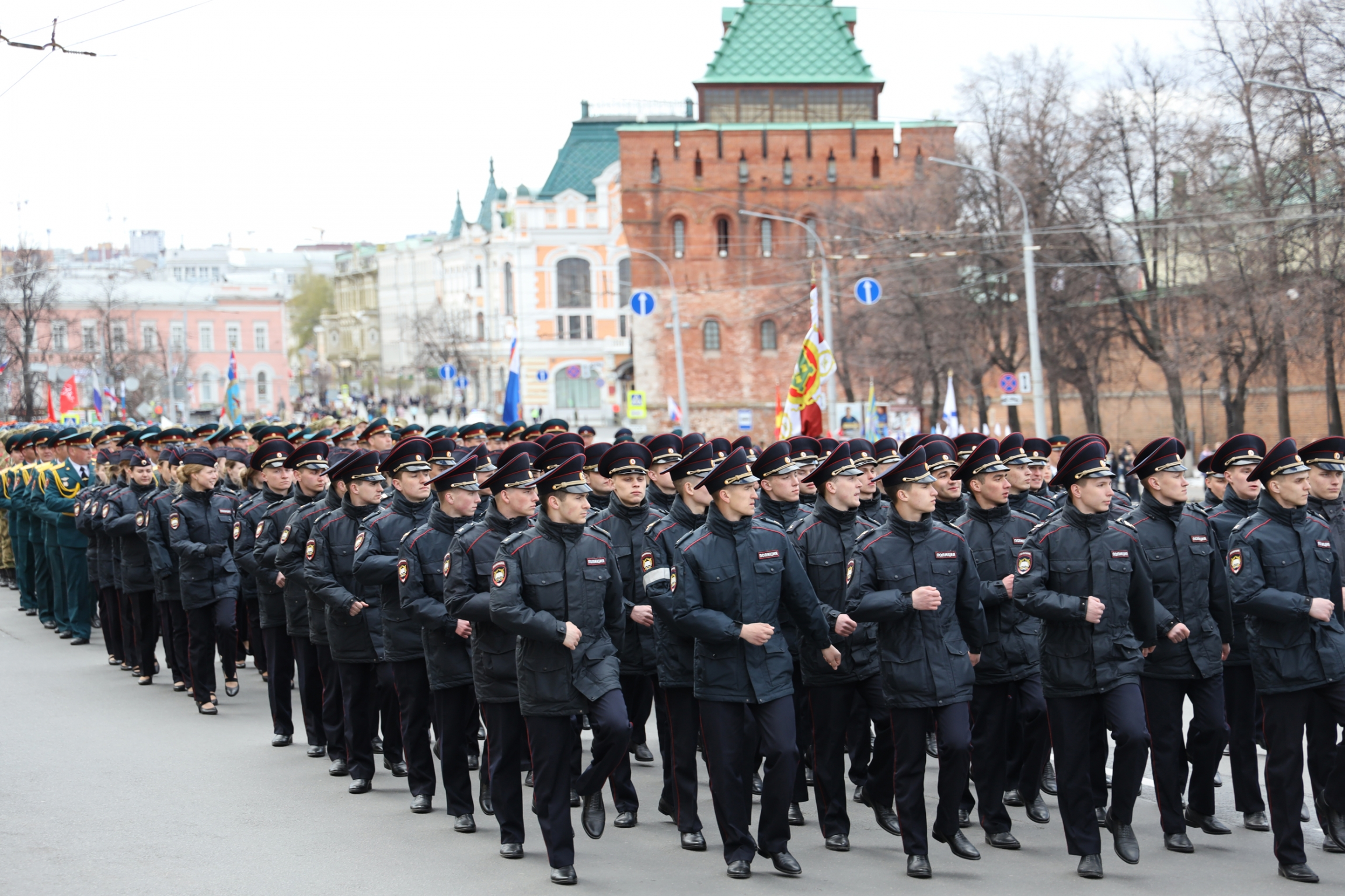 Men in miltary uniforms and formation march down a street