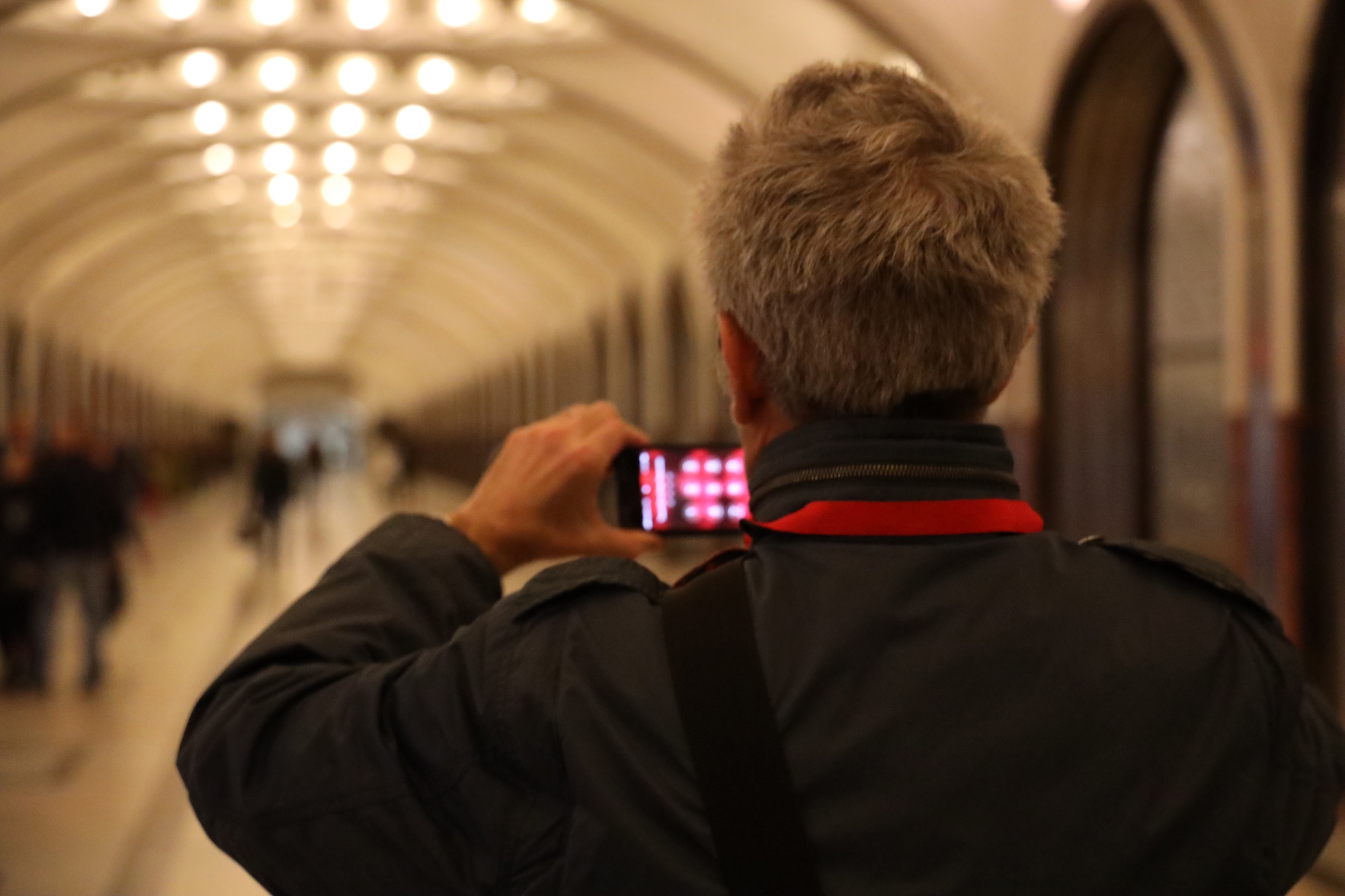 A man takes a photo of a train station on his cell phone