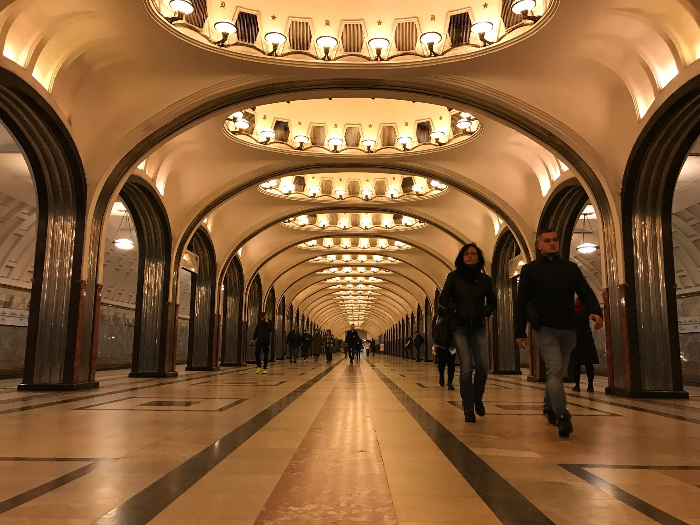 People walk through a gleaming train station
