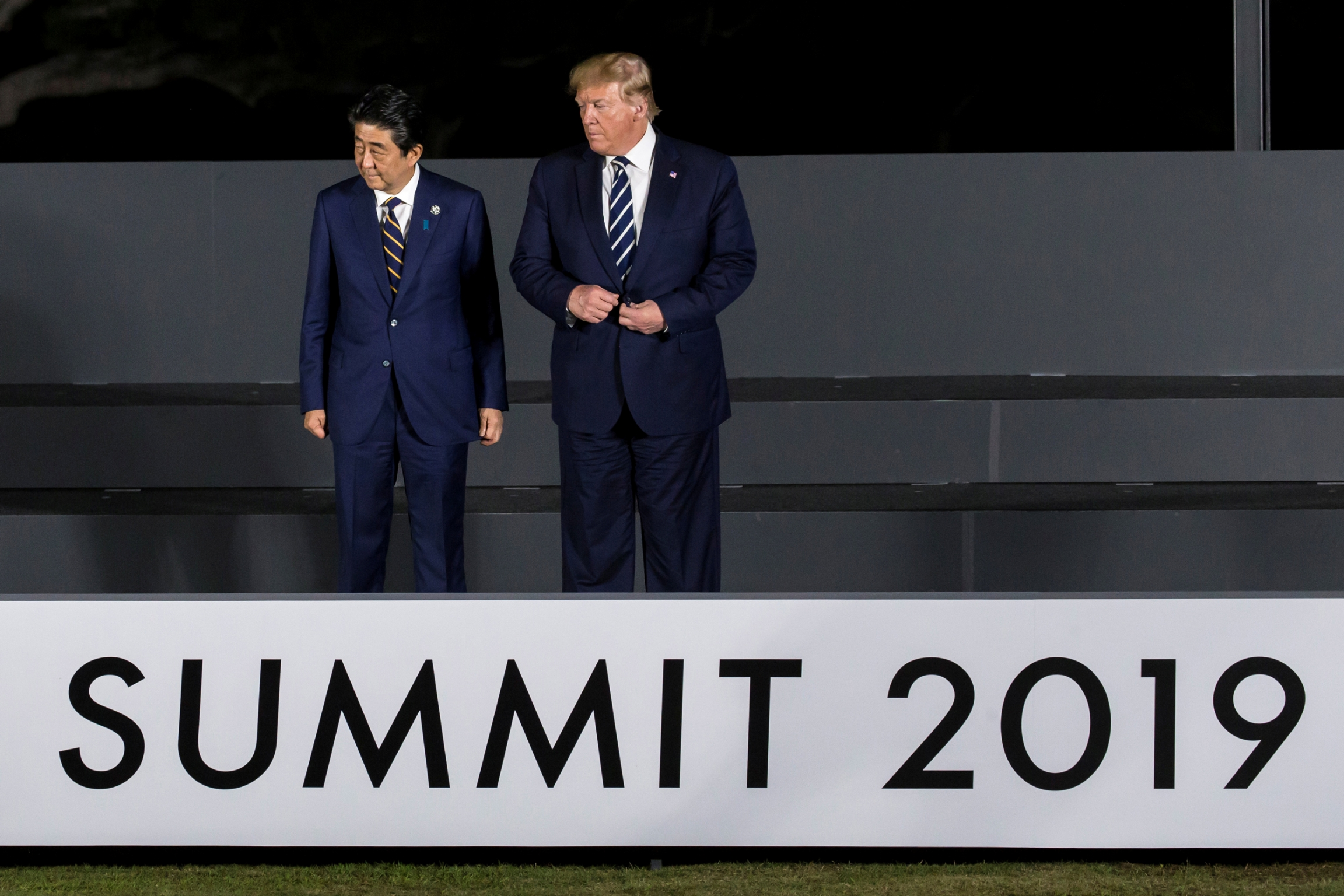 US President Donald Trump stands with Japanese Prime Minister Shinzō Abe above a sign that says Summit 2019
