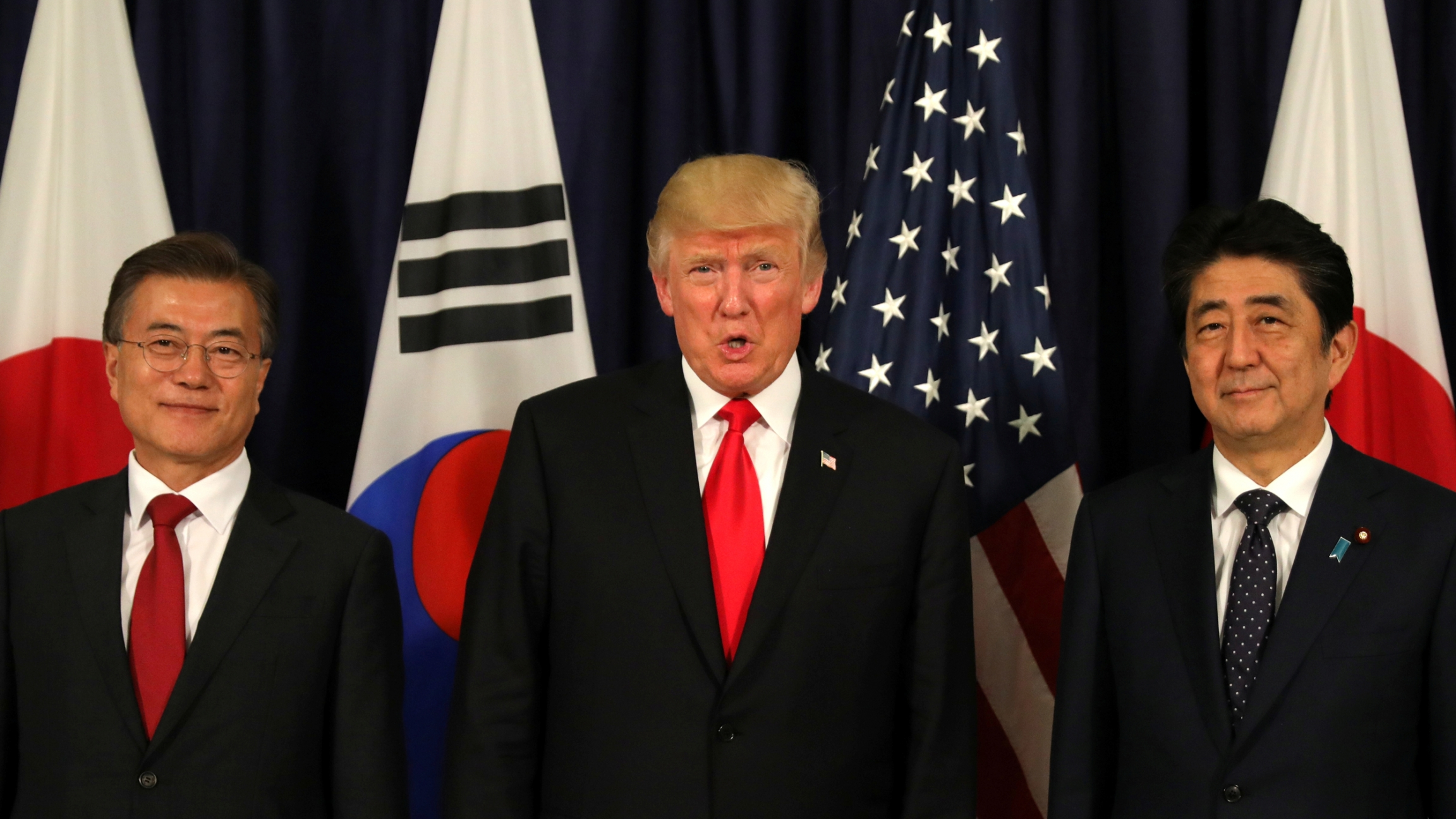 South Korean President Moon Jae-in, US President Donald Trump and Japanese Shinzō Abe stand in a line with flags form their countries behind them.
