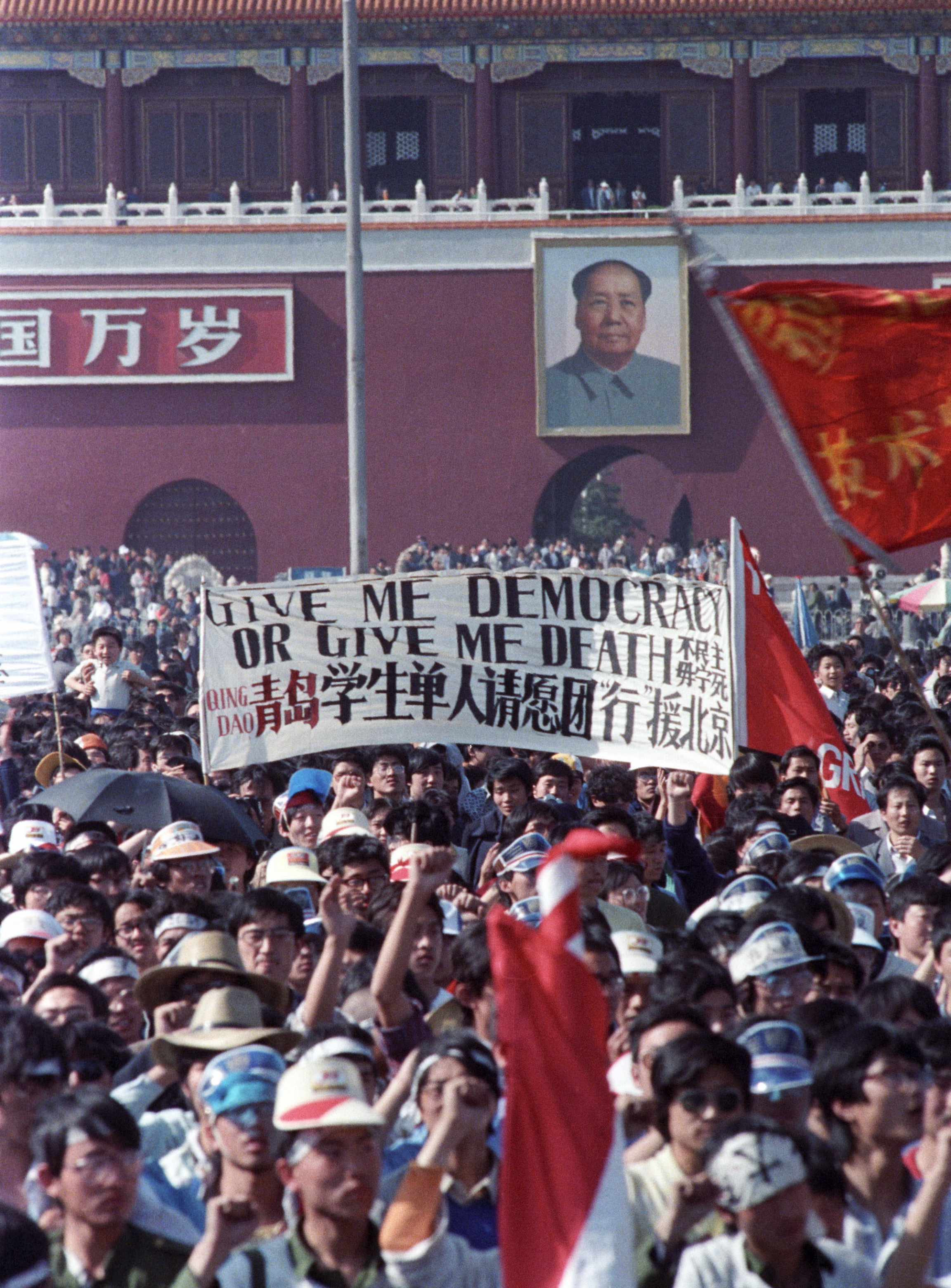 "Protesters crowd Tiananmen Square and carry a banner that says ""Give me democracy or give me death."""