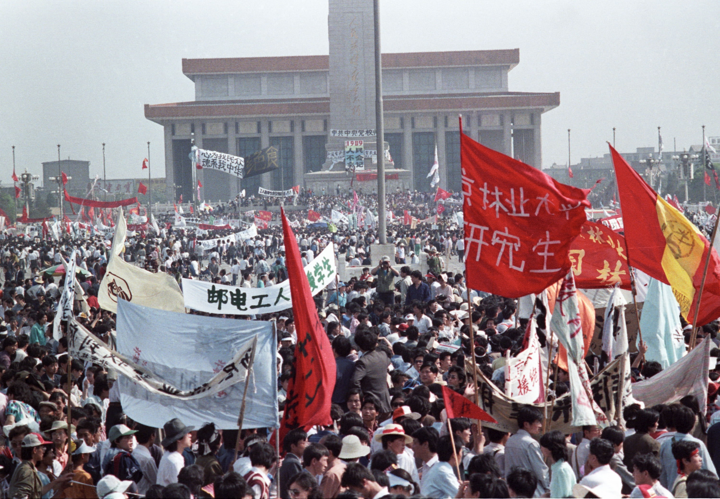 Crowds protest in Tiananmen Square carrying banners written in Chinese.