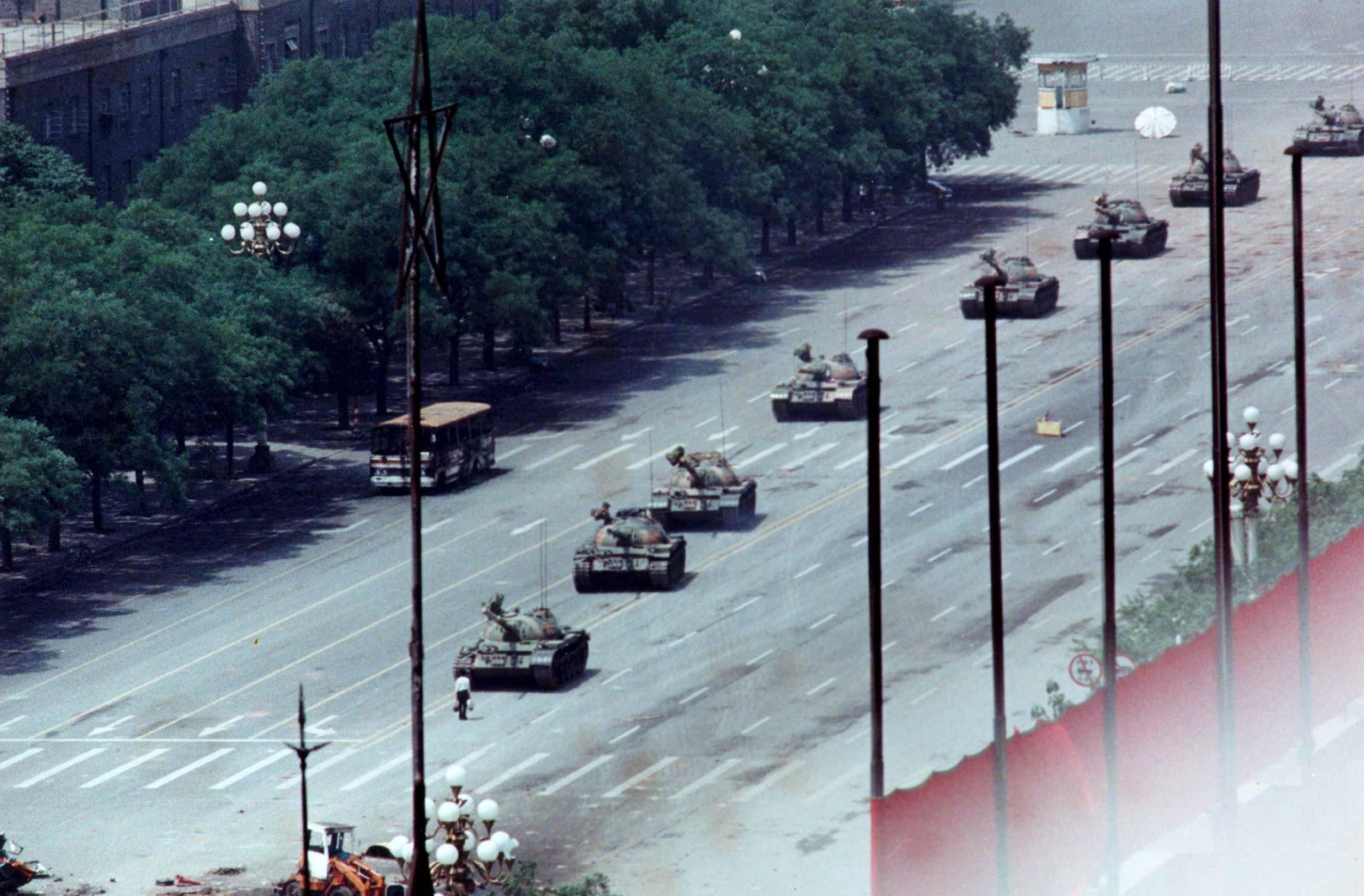 A man defiantly stands in front of a line line of tanks.