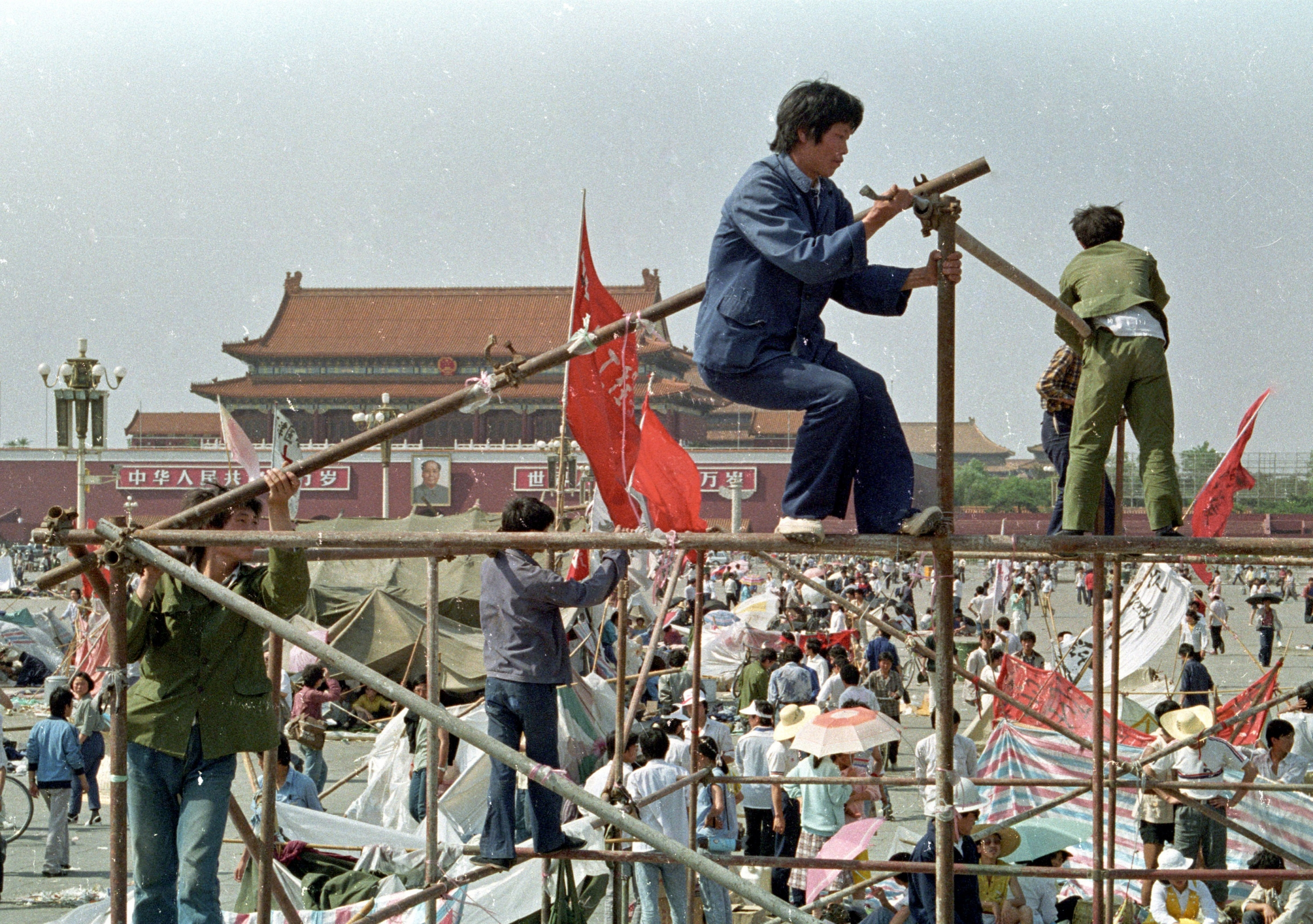Students prop up wooden poles to build tents in Tiananmen Square.