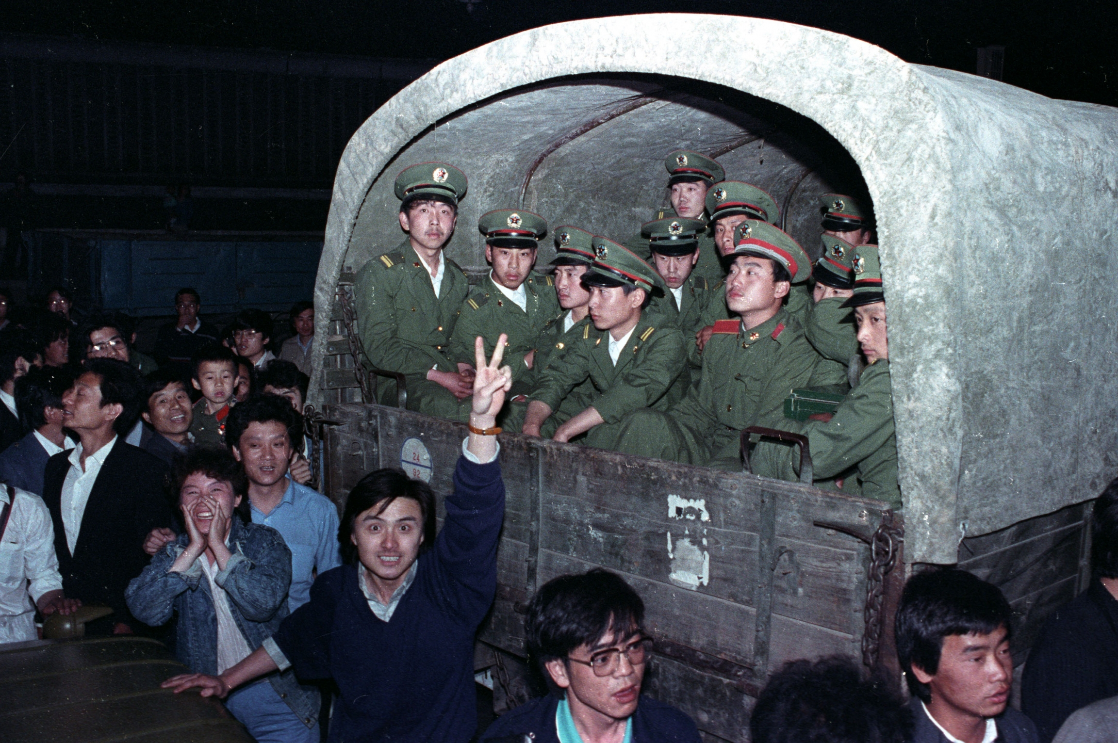 At night a group of students surround a military vehicle.