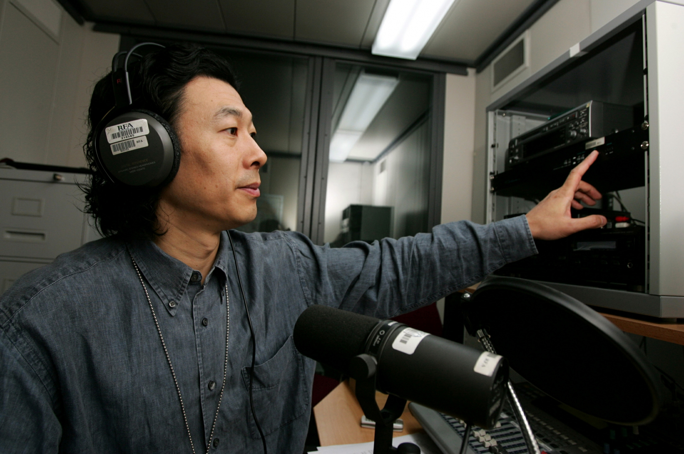 A man with headphones on speaks into a microphone in a studio.