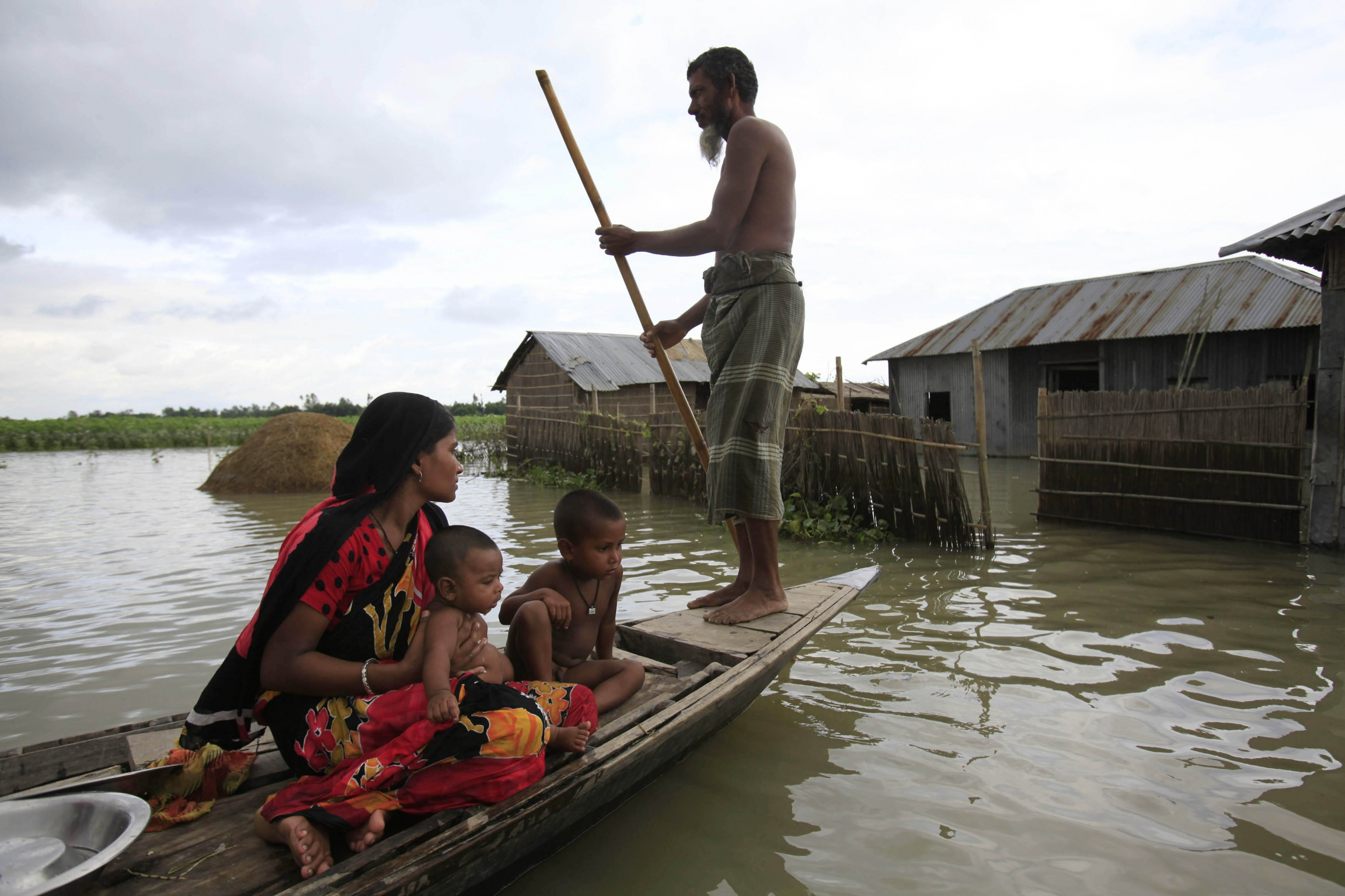 A family sits on a small boat in a flooded village.