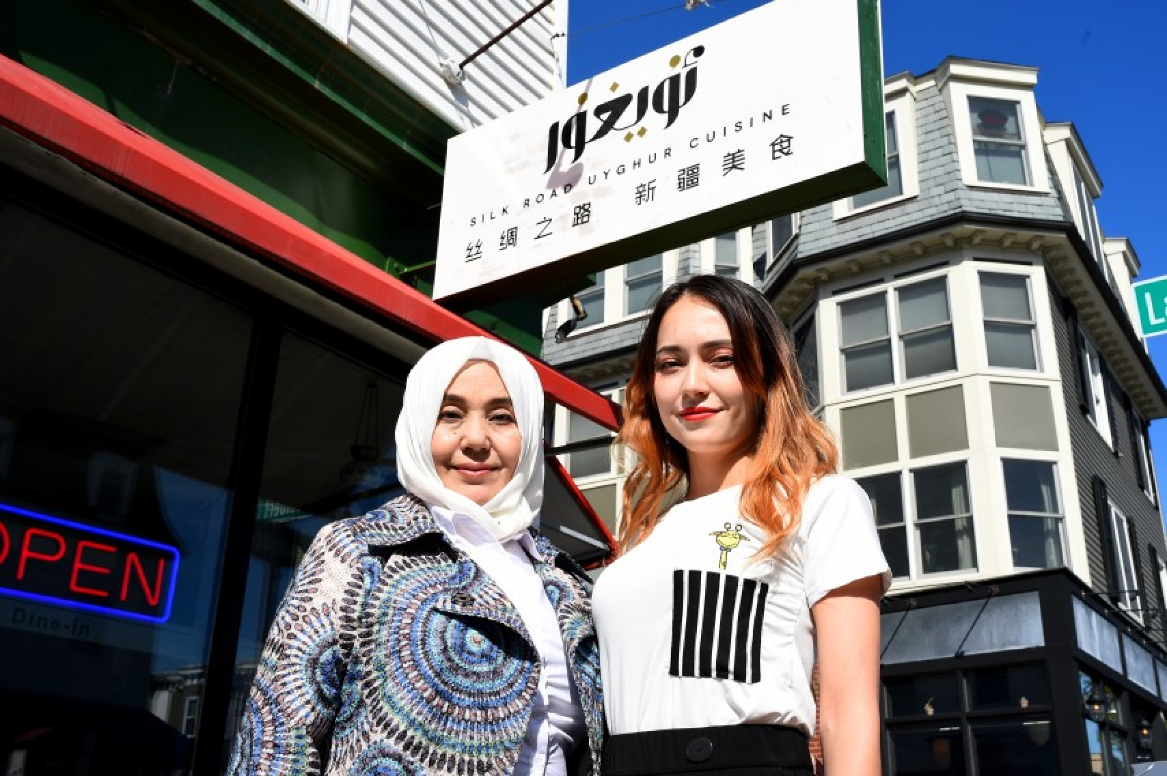 Two women stand outside a restaurant