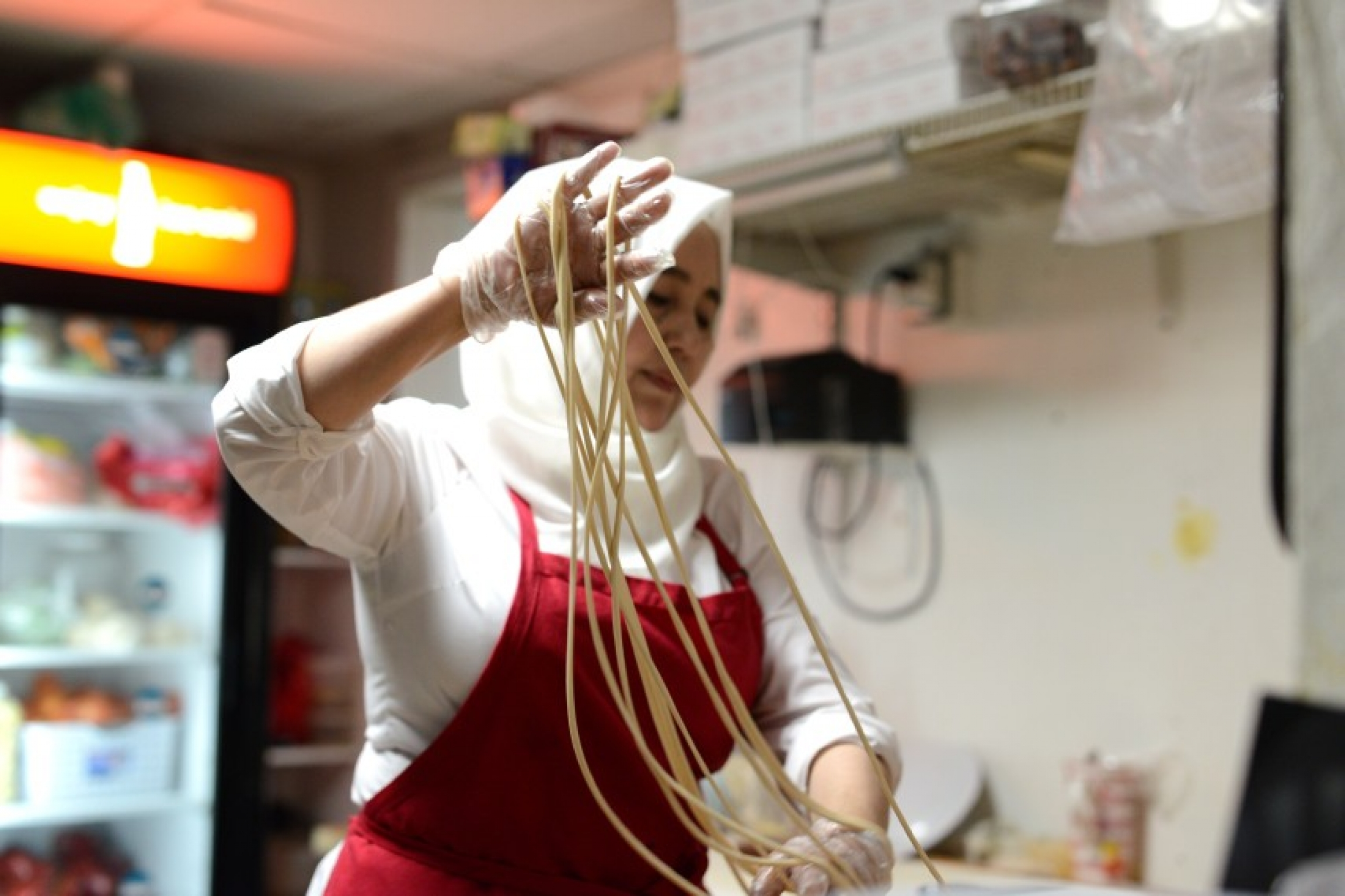 A woman in a kitchen makes noodles.