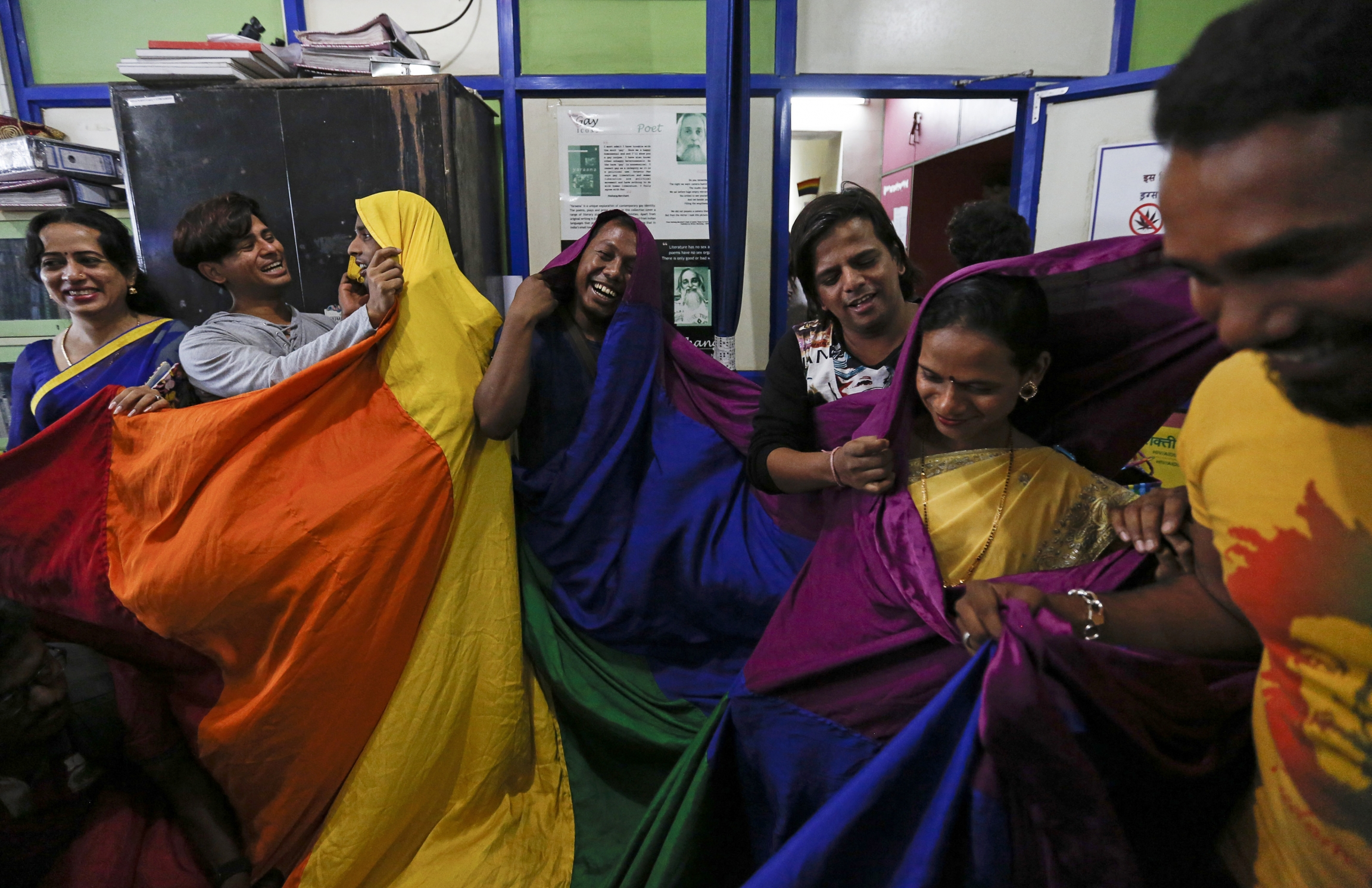 Gay rights activists in India celebrate and cover themselves in rainbow flags.