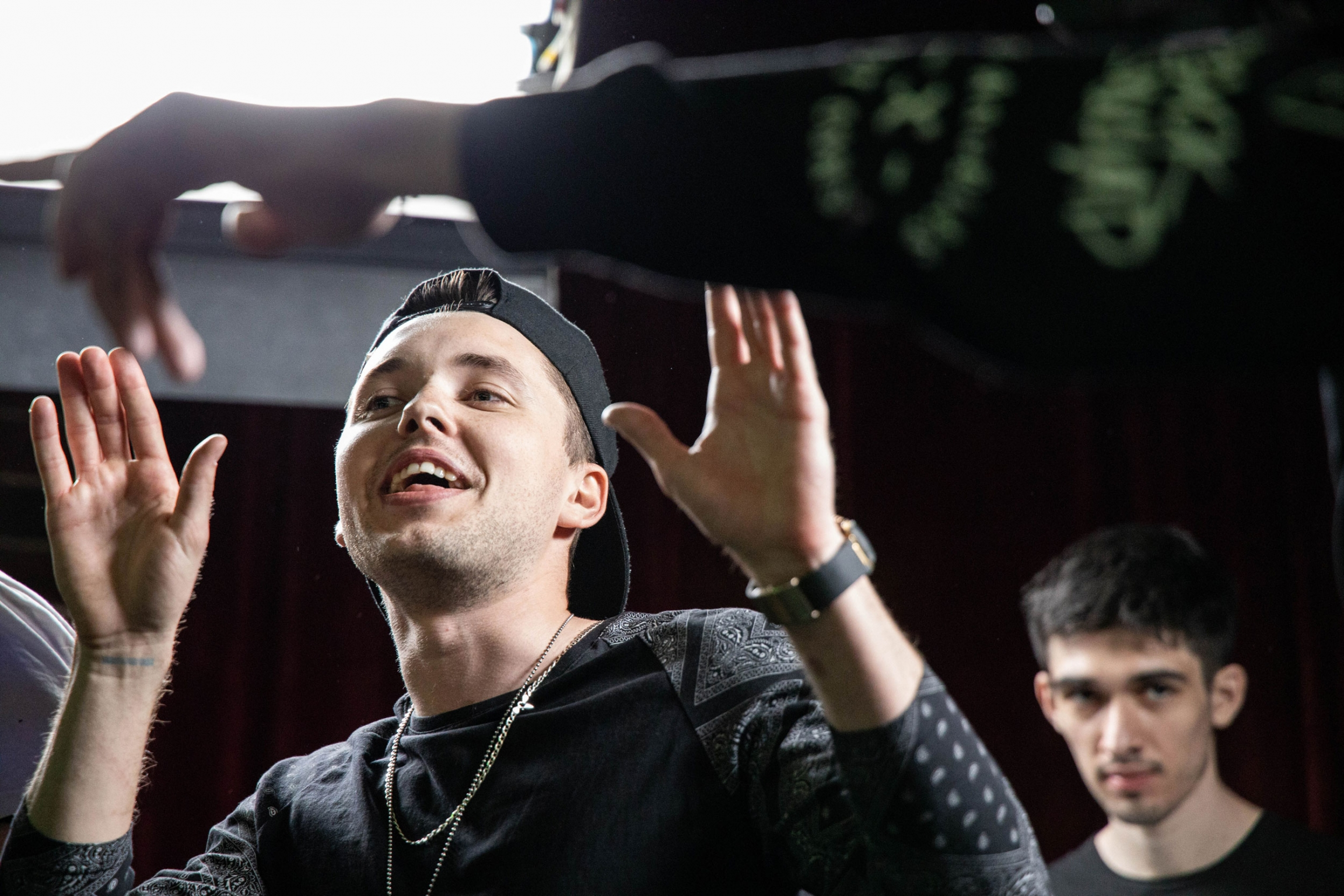 A rapper raises his hands at a crowd.
