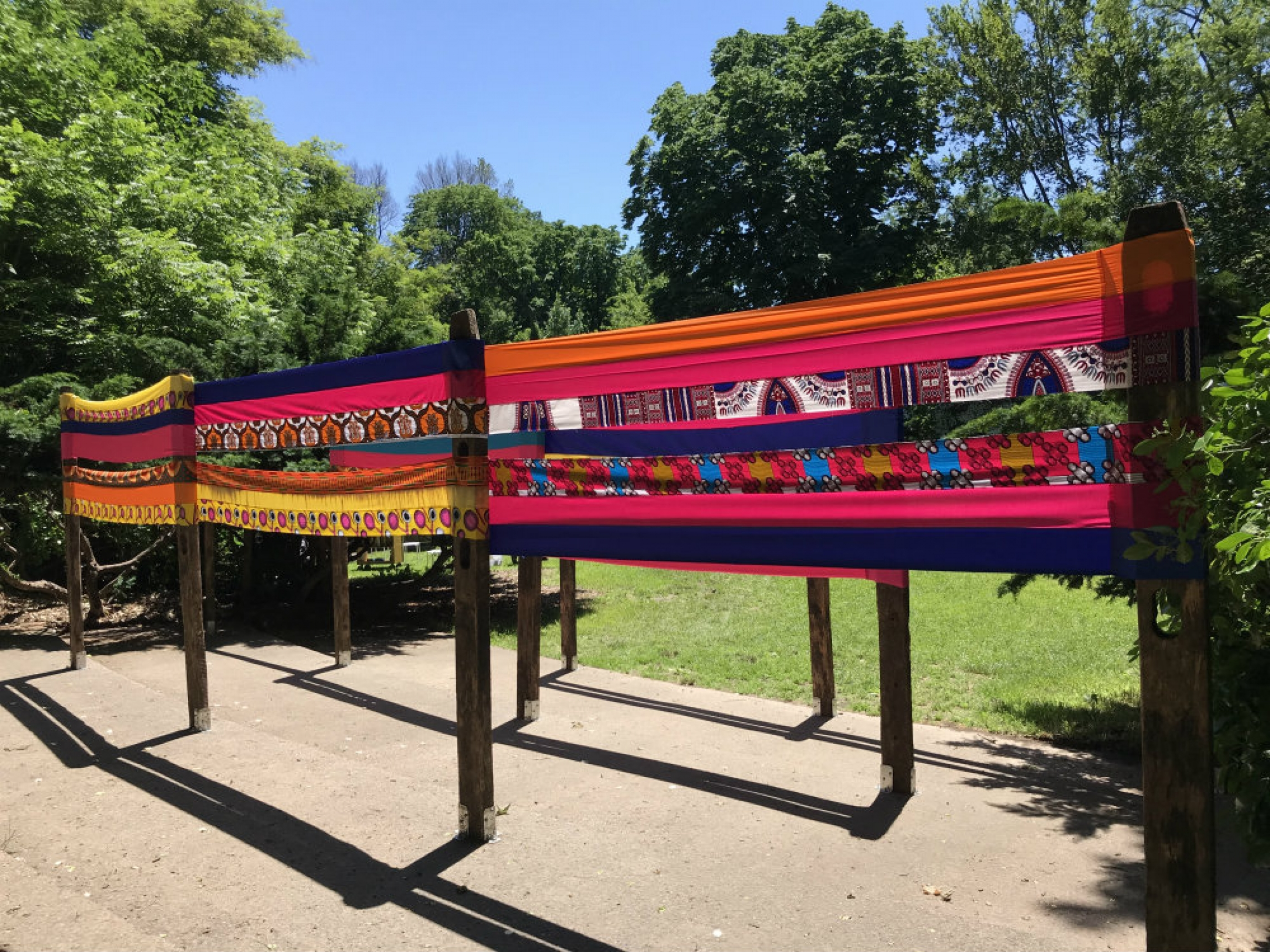An art installation that includes bright cloth around several posts.