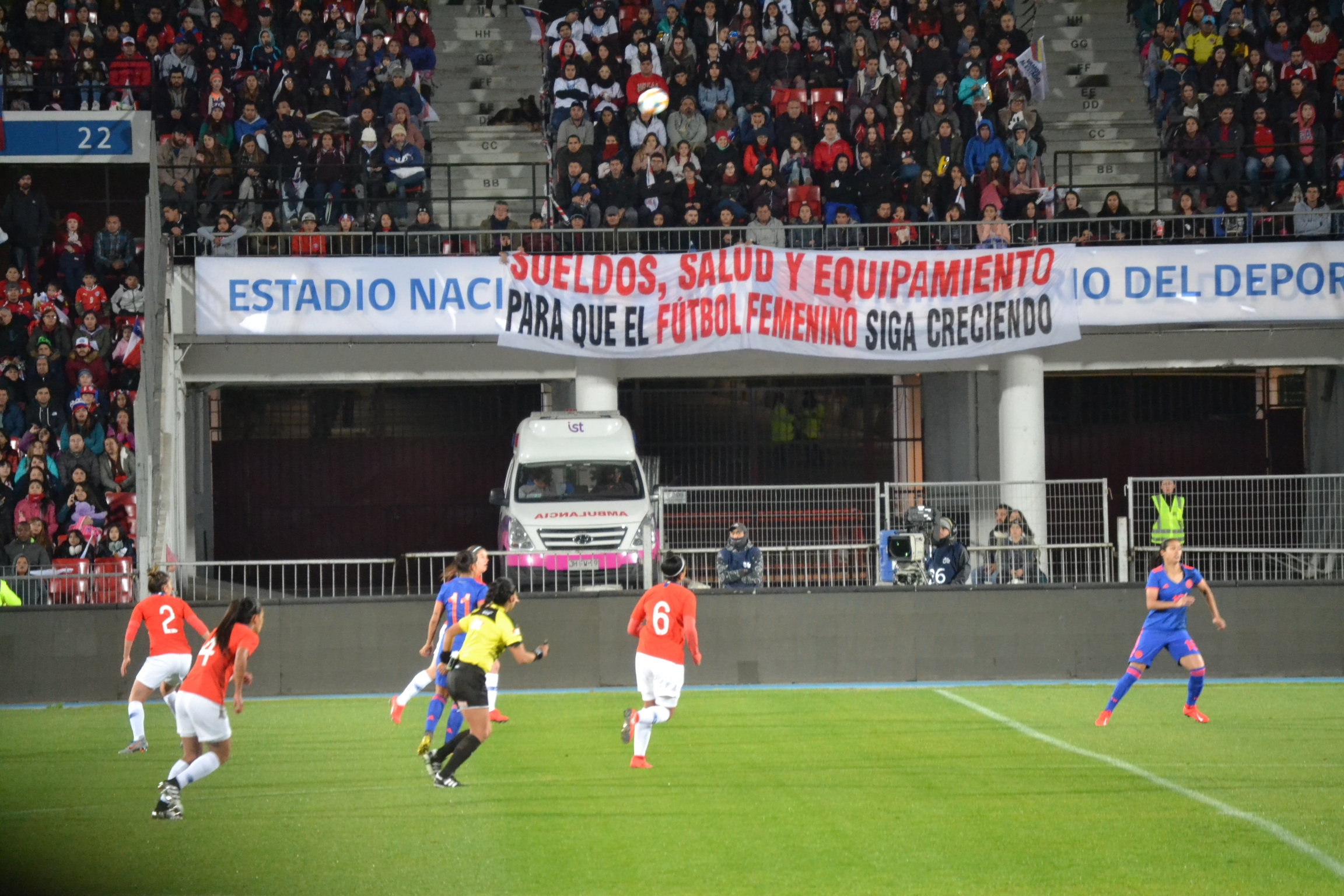 A sign on women's rights held in stadium during women's soccer match.