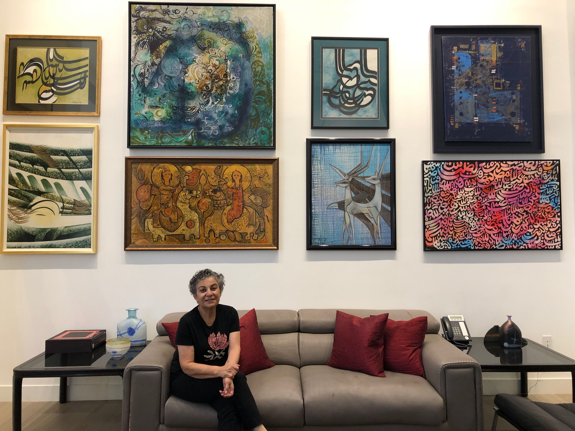 A woman sits on a couch with several works of art behind her.