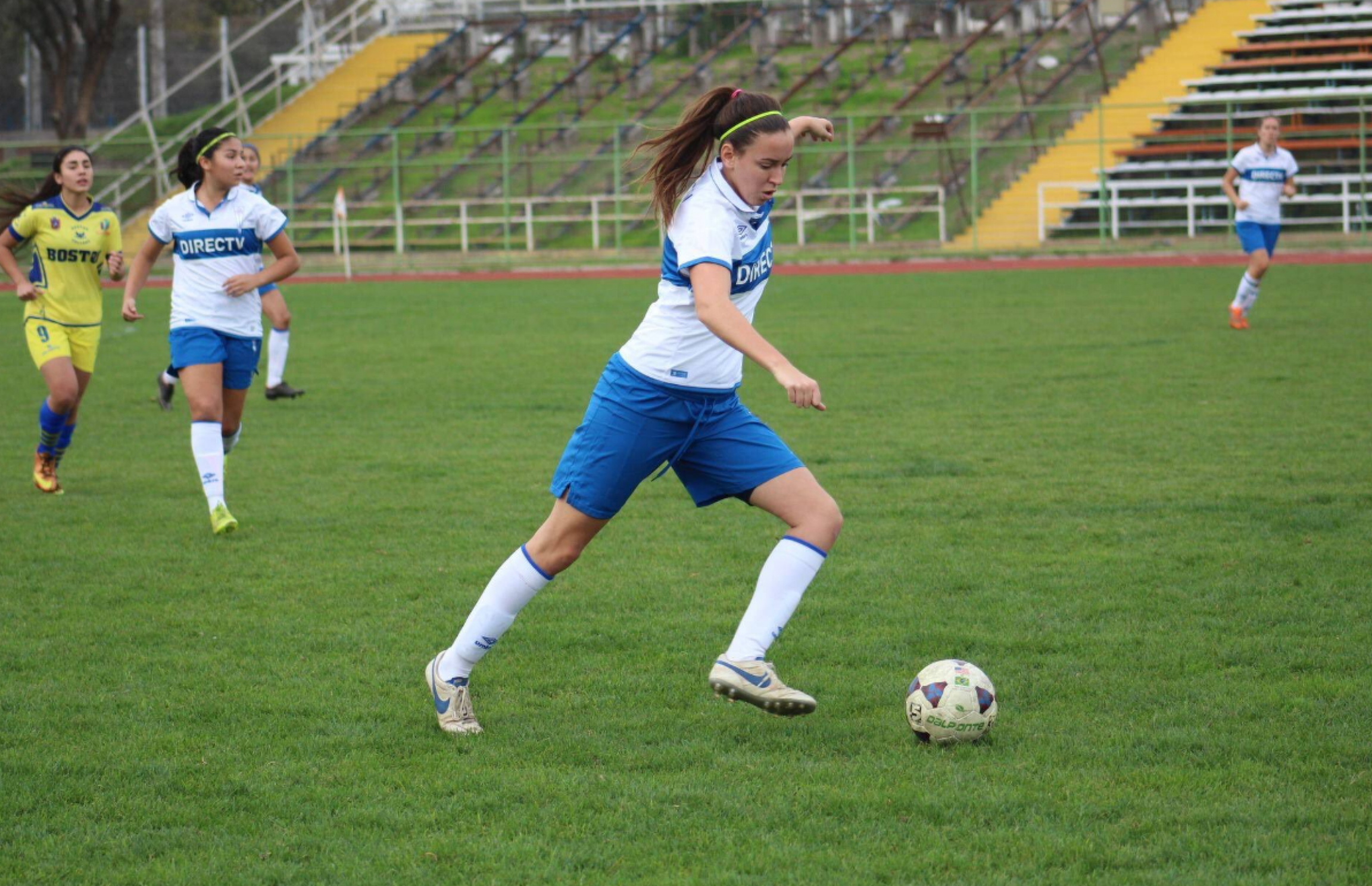 A woman wears a blue and white uniform and kicks a soccer ball.