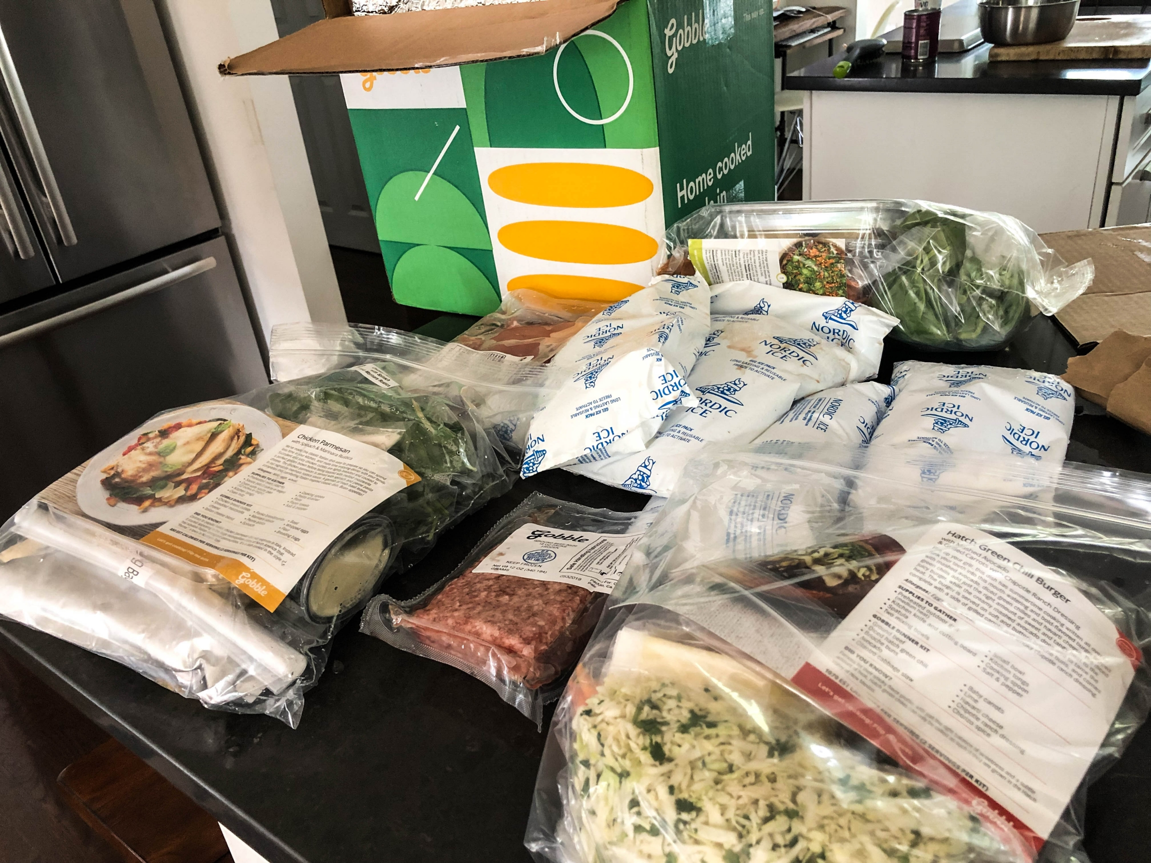 A meal kit is unboxed on a counter space. Food is wrapped in plastic packaging.